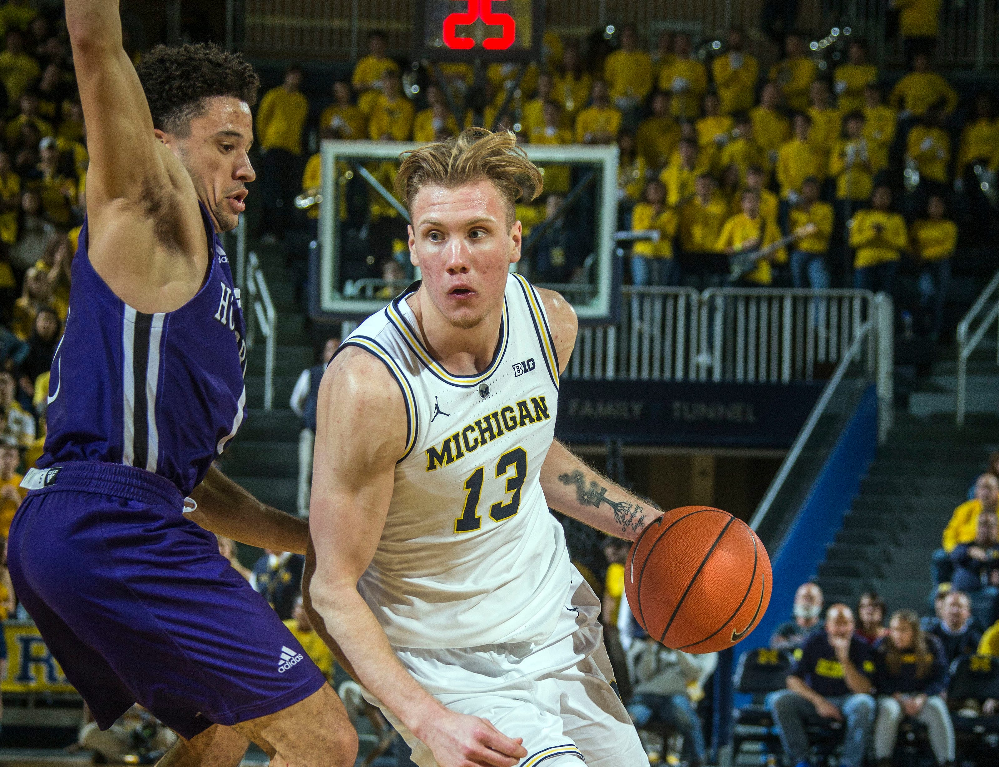 Holy Cross guard Caleb Green, left, defends against Michigan forward Ignas Brazdeikis (13) in the second half of an NCAA college basketball game at Crisler Center in Ann Arbor, Mich., Saturday, Nov. 10, 2018. (AP Photo/Tony Ding)