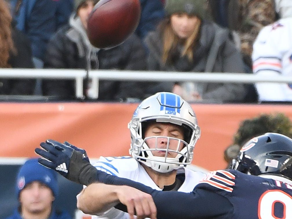 Lions quarterback Matthew Stafford gets a pass off with pressure from Bears' Leonard Floyd late in the fourth quarter.