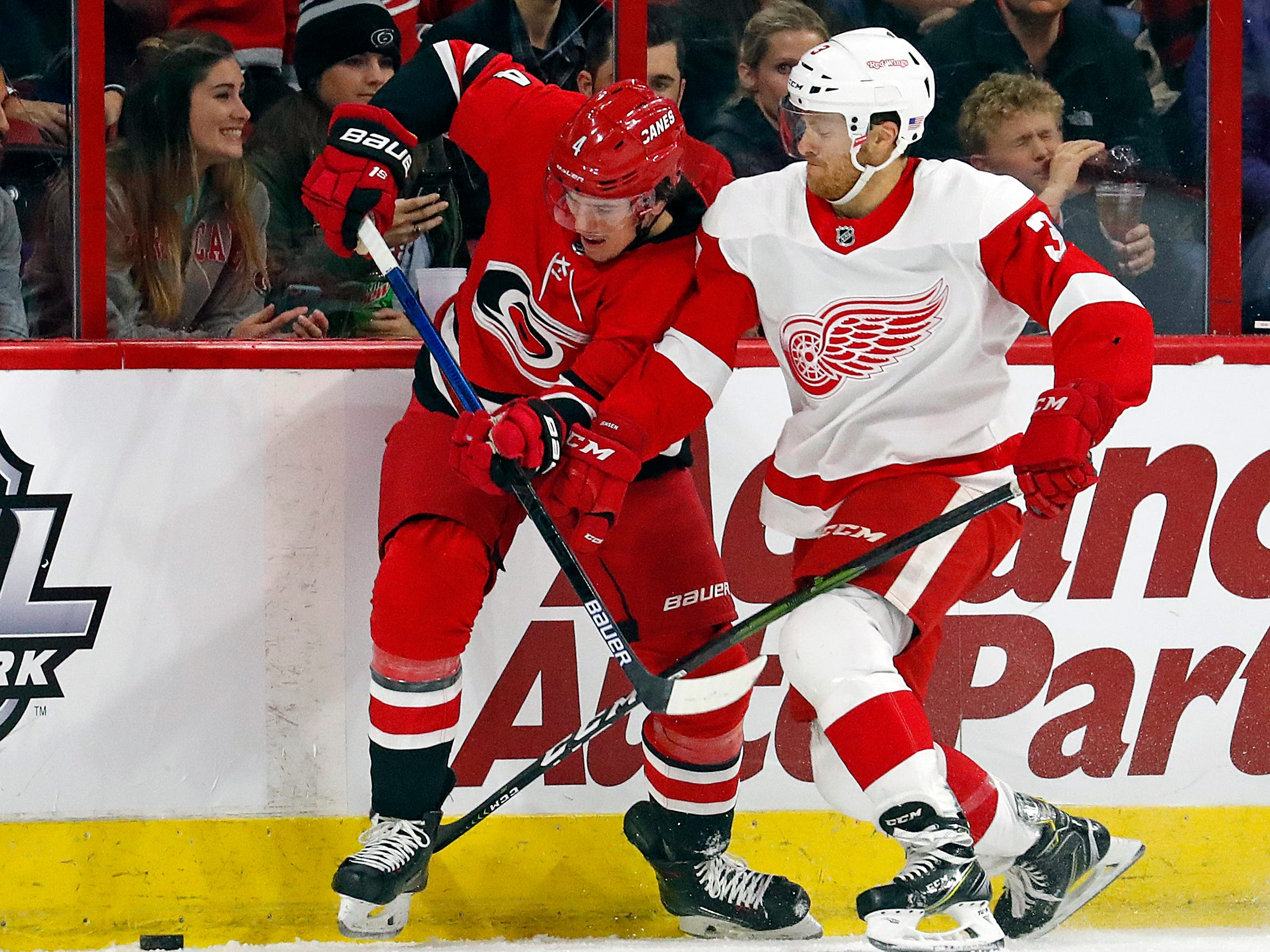 Carolina Hurricanes' Haydn Fleury (4) battles with Detroit Red Wings' Nick Jensen (3) against the boards during the first period.