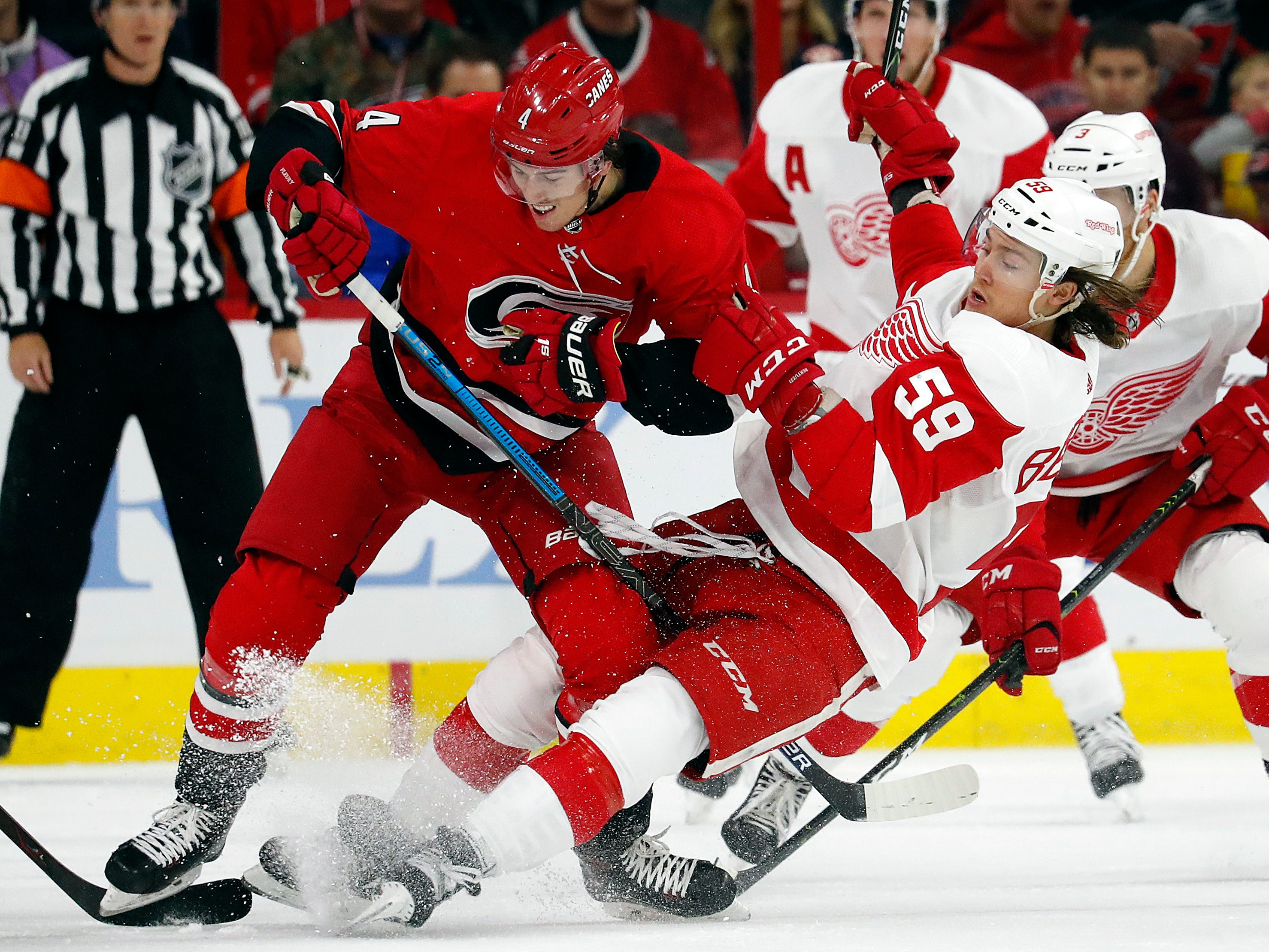 Carolina Hurricanes' Haydn Fleury (4) collides with Detroit Red Wings' Tyler Bertuzzi (59) during the first period of an NHL hockey game Saturday, Nov. 10, 2018, in Raleigh, N.C. The Red Wings won the game, 4-3 in a shootout.