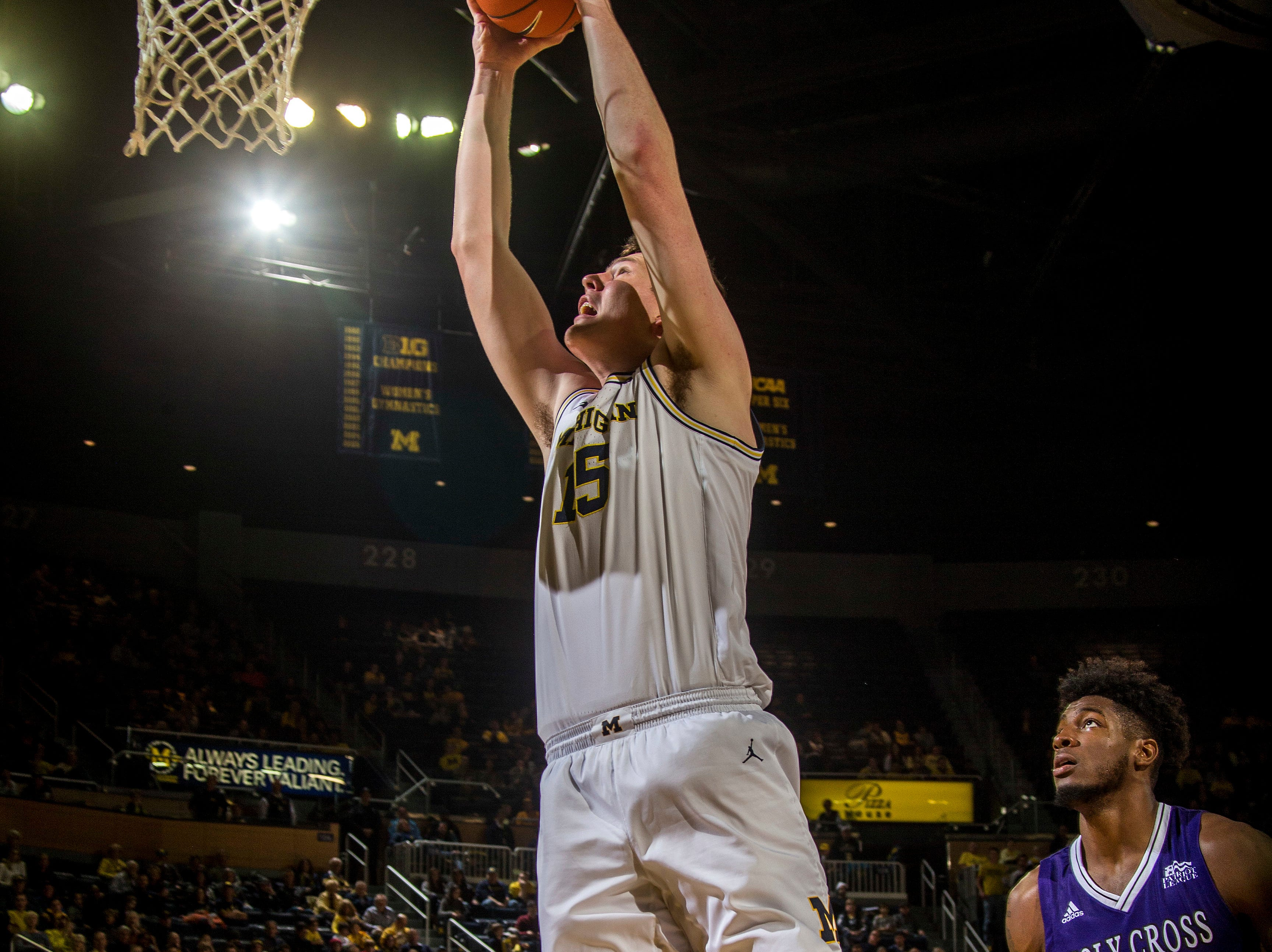 Michigan center Jon Teske (15) dunks the ball while watched by Holy Cross forward Jehyve Floyd (30) in the second half of an NCAA college basketball game at Crisler Center in Ann Arbor, Mich., Saturday, Nov. 10, 2018. (AP Photo/Tony Ding)