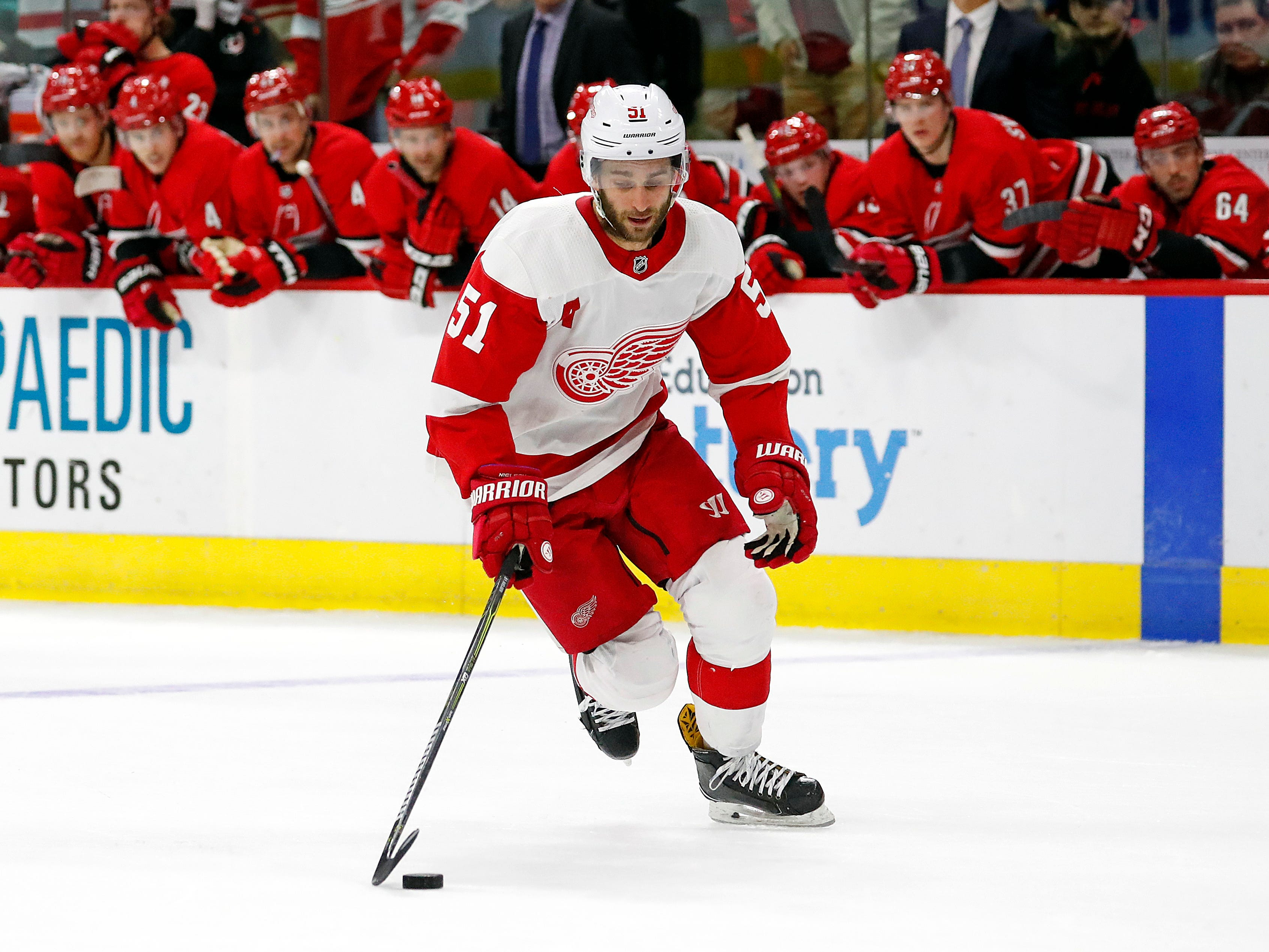 Detroit Red Wings' Frans Nielsen (51) brings the puck up the ice during the third round of the shootout as the Carolina Hurricanes watch from the bench.