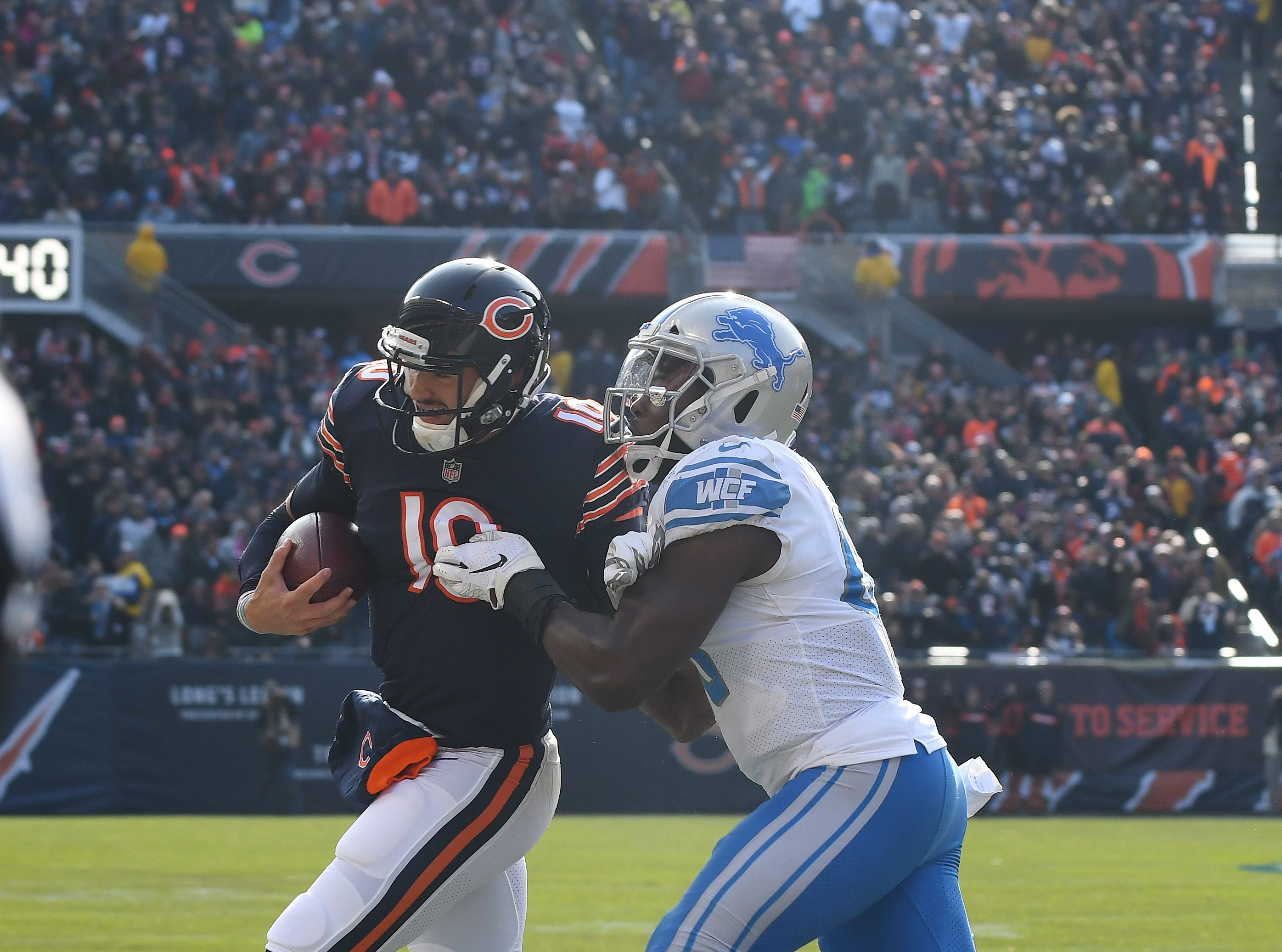 Lions' Jarrad Davis continues to shove Bears quarterback Mitchell Trubisky after going out of bounds and picks up a penalty during a Chicago offensive drive in the second quarter.