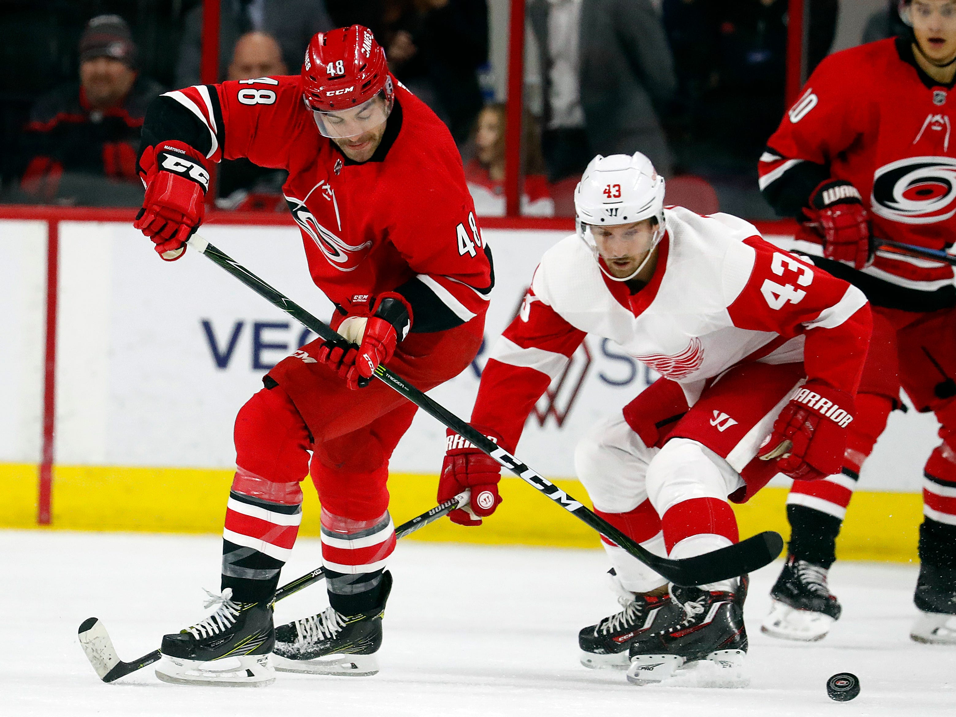 Carolina Hurricanes' Jordan Martinook (48) has the puck tipped away by Detroit Red Wings' Darren Helm (43) during the first period.