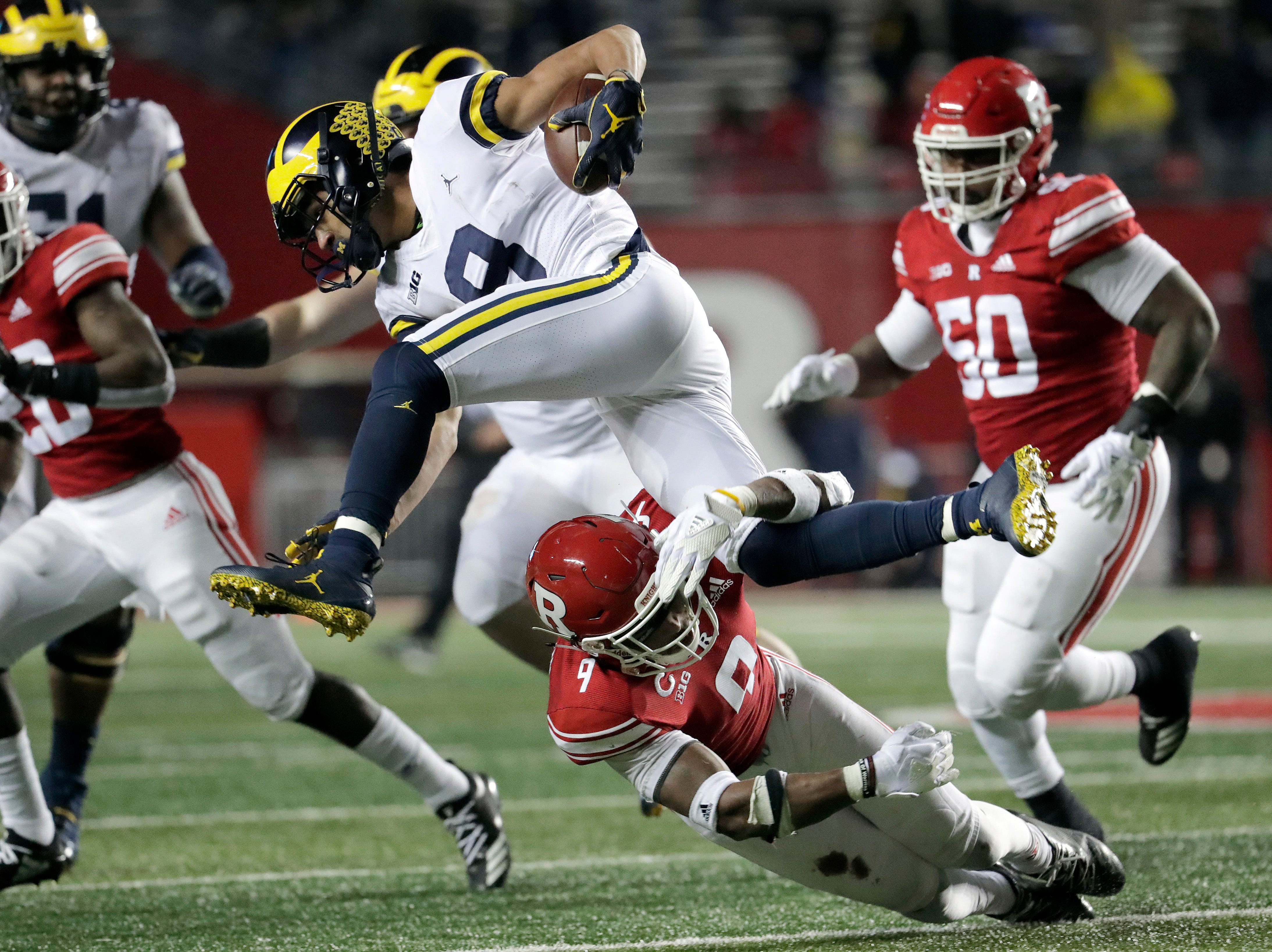 Michigan wide receiver Ronnie Bell, top, tries to leap over the tackle of Rutgers defensive back Saquan Hampton (9).