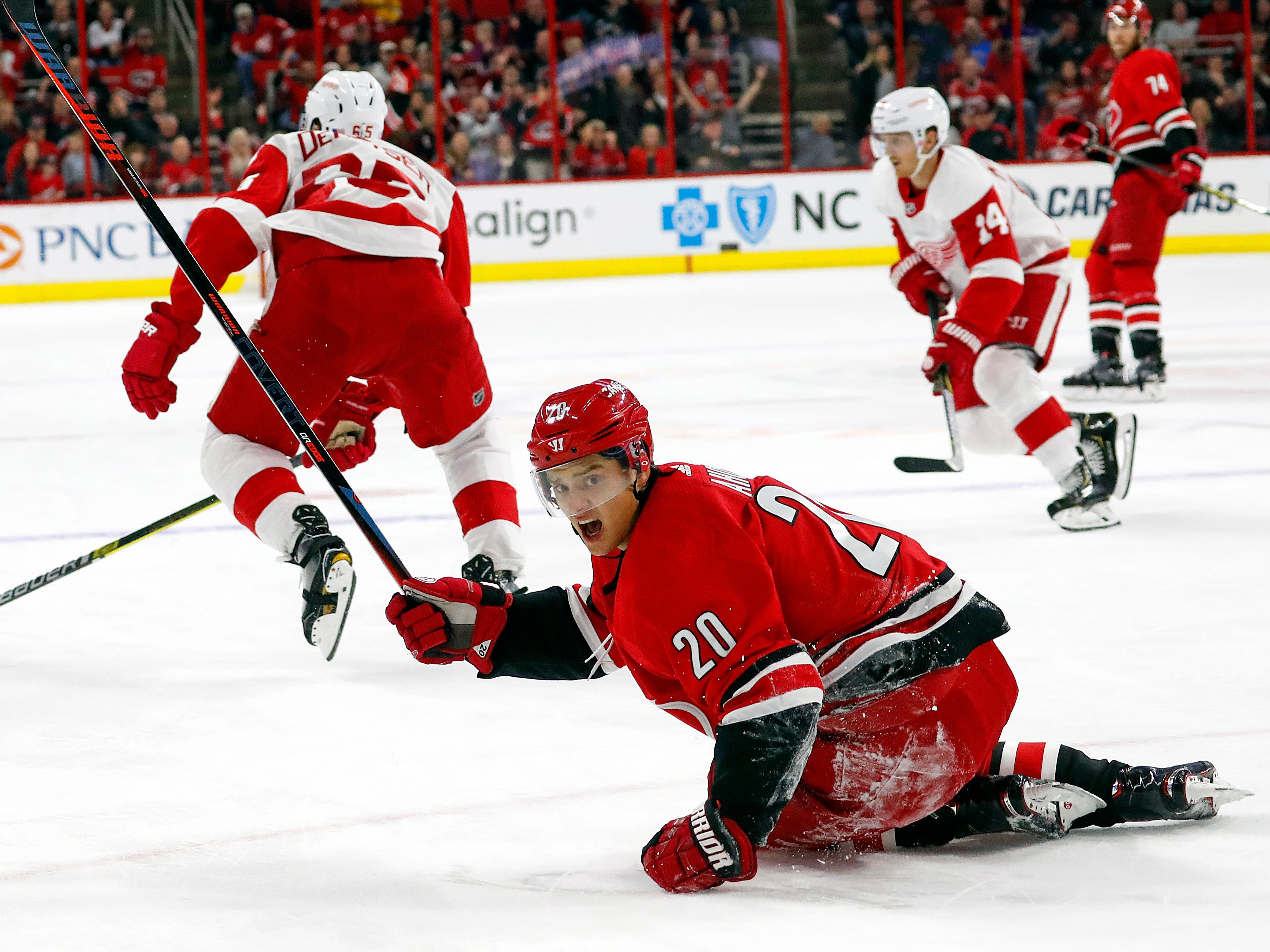 Carolina Hurricanes' Sebastian Aho (20) looks toward an official after being tripped by Detroit Red Wings' Danny DeKeyser (65) during overtime.