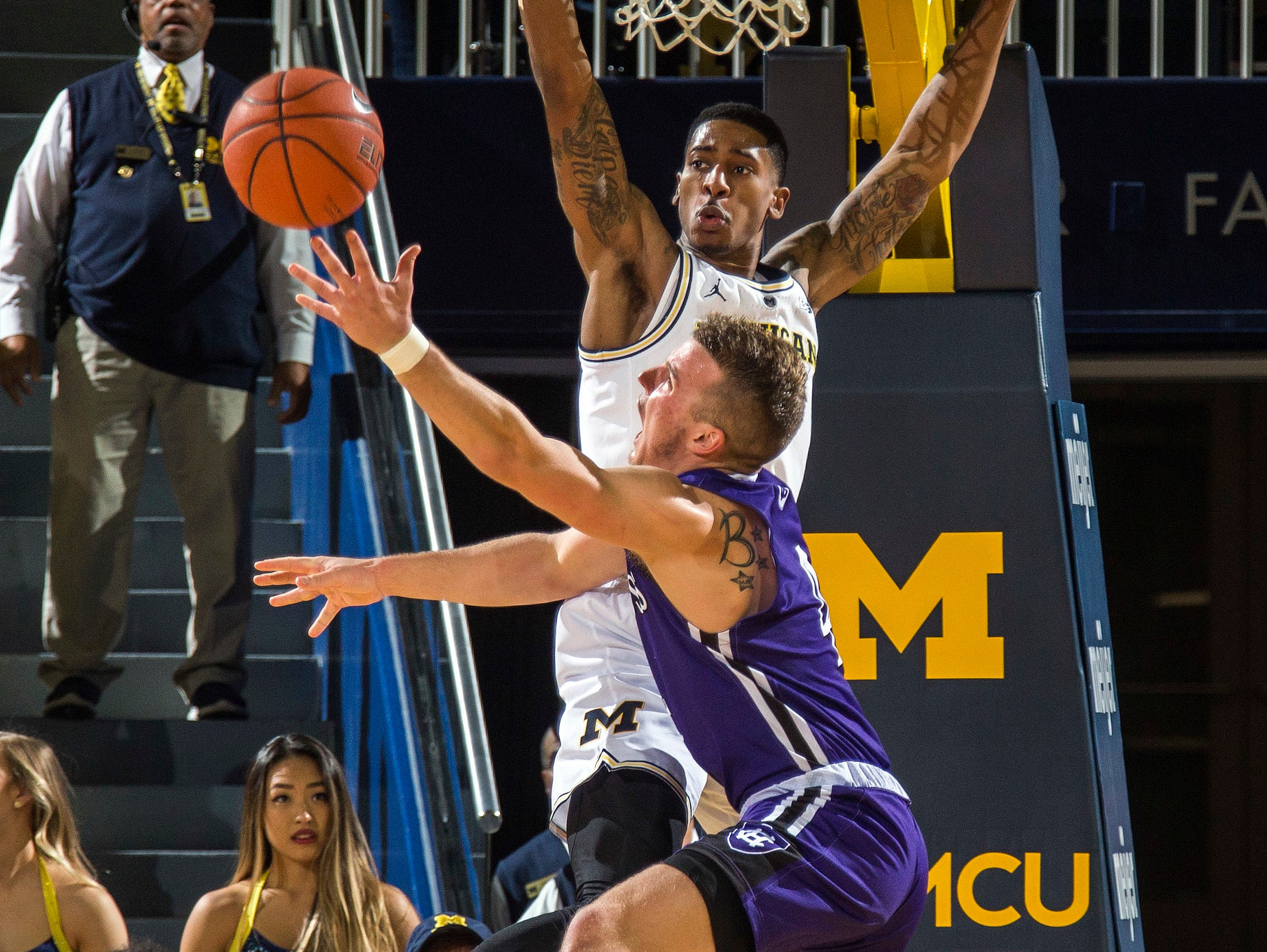 Holy Cross guard Austin Butler, front, attempts to make a basket while defended by Michigan guard Charles Matthews, back, in the second half of an NCAA college basketball game at Crisler Center in Ann Arbor, Mich., Saturday, Nov. 10, 2018. (AP Photo/Tony Ding)