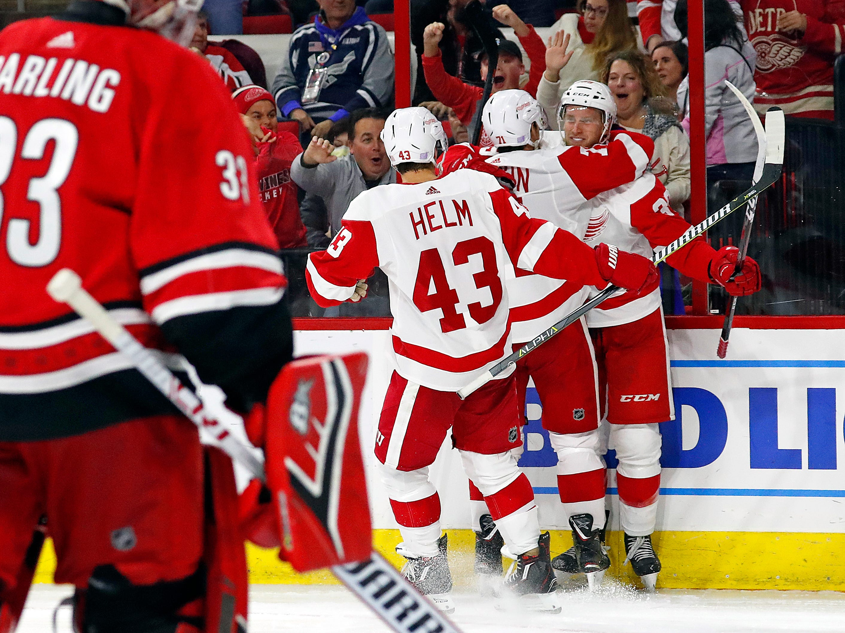 Detroit Red Wings' Anthony Mantha (39) celebrates his second goal of the night with teammates Dylan Larkin (71) and Darren Helm (43) against the Carolina Hurricanes during the third period.