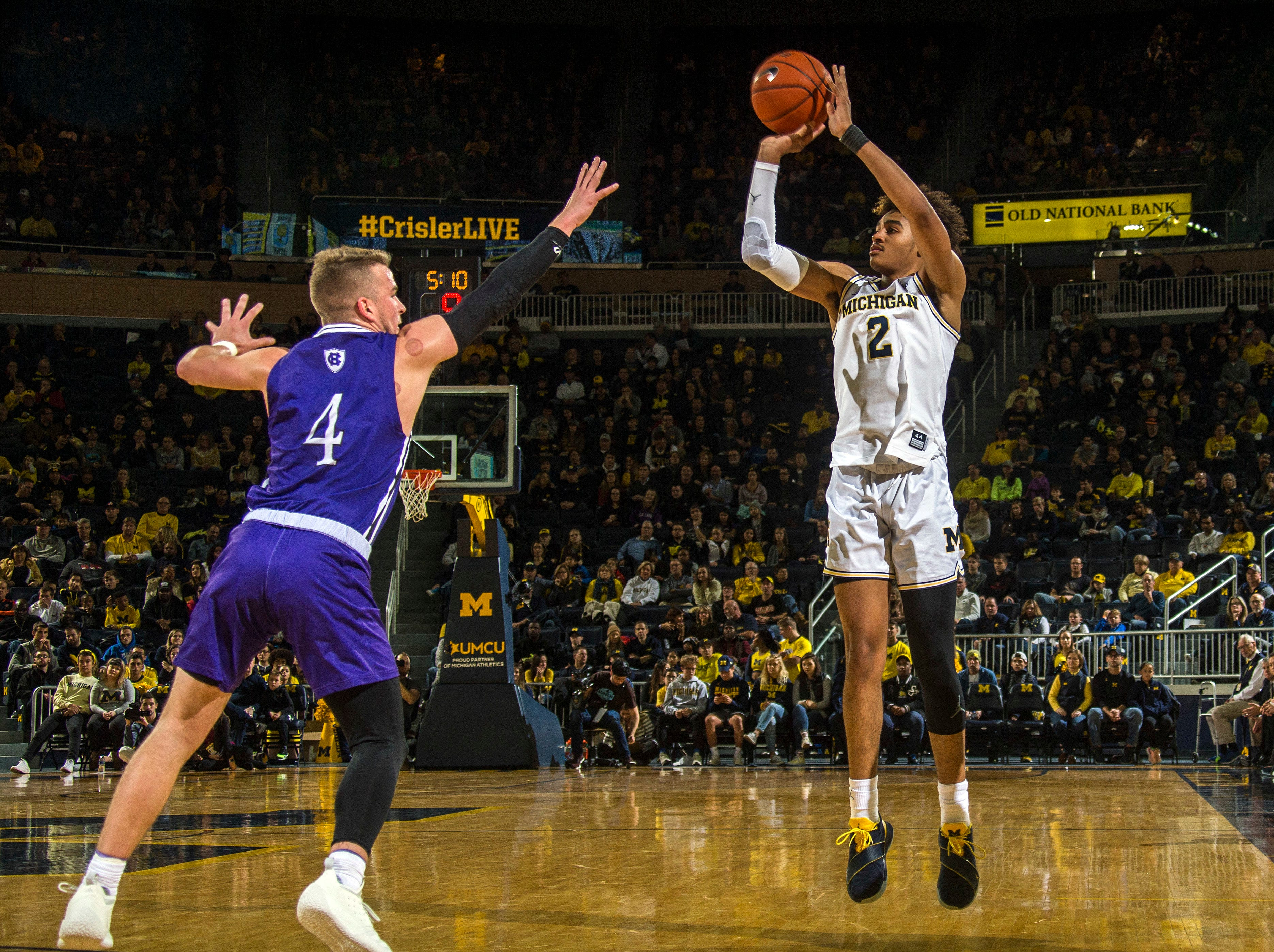 Holy Cross guard Austin Butler (4) defends a 3-point attempt from Michigan guard Jordan Poole (2) during the first half.