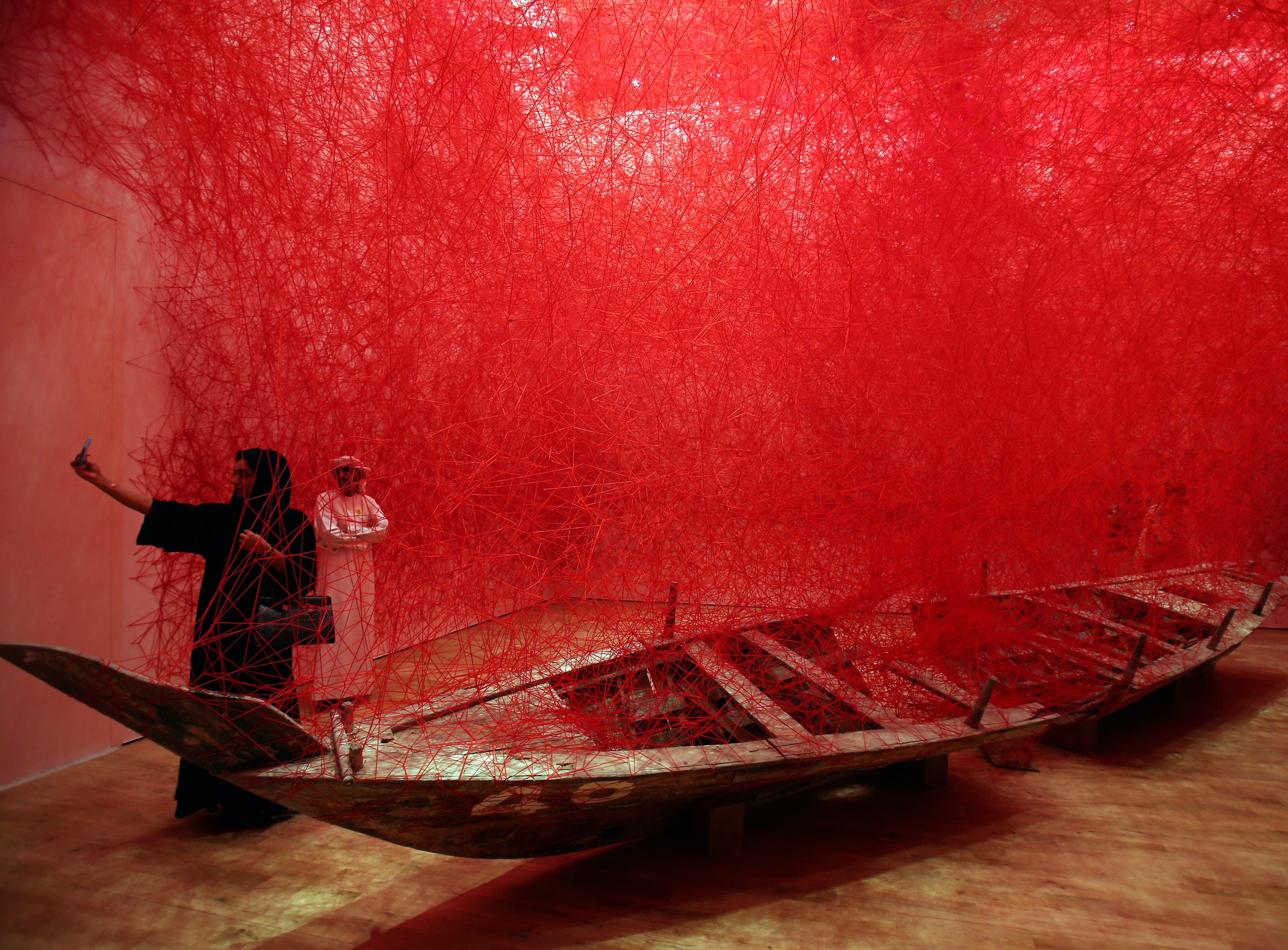 "A woman takes selfie in front of the ""Departure"" installation by Japanese artist Chiharu Shiota during the launch of Jameel Arts Centre in Dubai, United Arab Emirates, Sunday, Nov. 11, 2018."