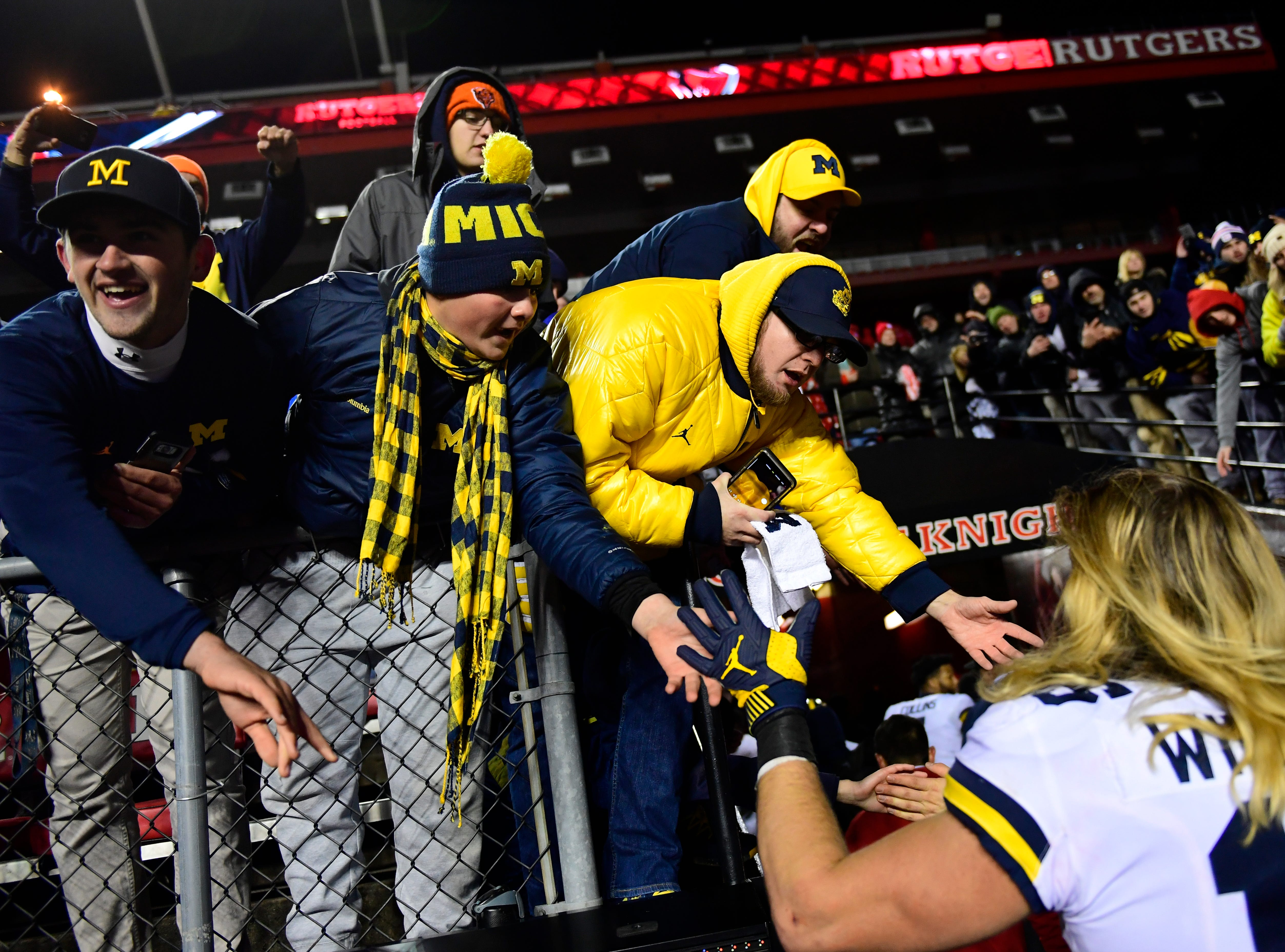 Michigan fans high-five Chase Winovich after the game.