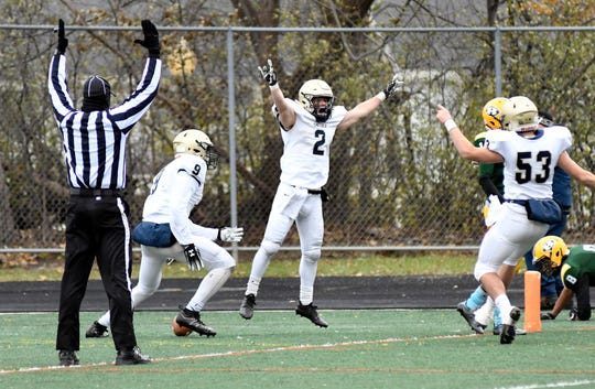 Chelsea running back Aaron McDaniels (2) celebrates with teammates after scoring the winning touchdown against Farmington Hills Harrison with less than a minute left left in the fourth quarter on Saturday.