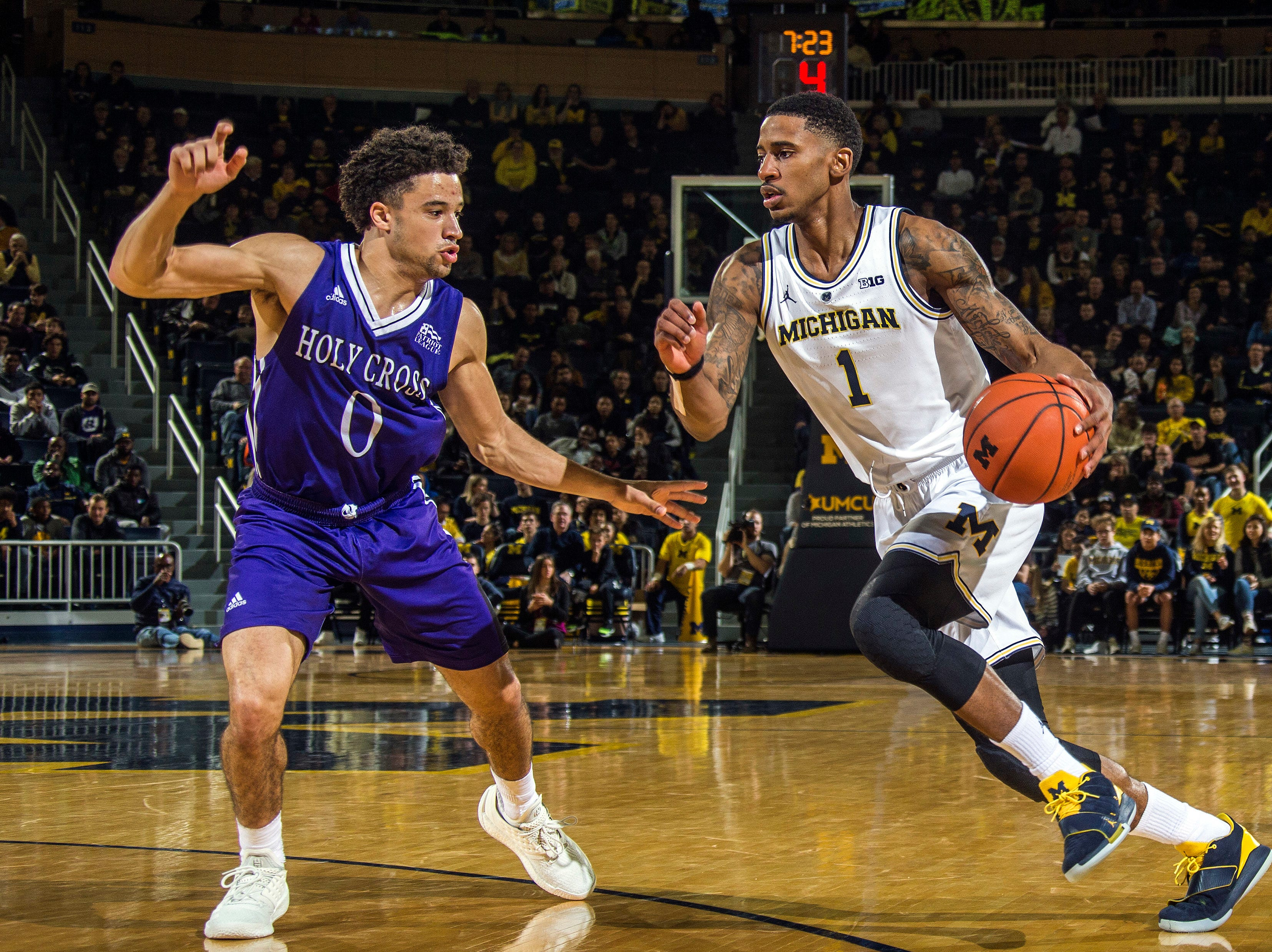 Holy Cross guard Caleb Green (0) defends against Michigan guard Charles Matthews (1) during the first half of an NCAA college basketball game in Ann Arbor, Mich., Saturday, Nov. 10, 2018. (AP Photo/Tony Ding)