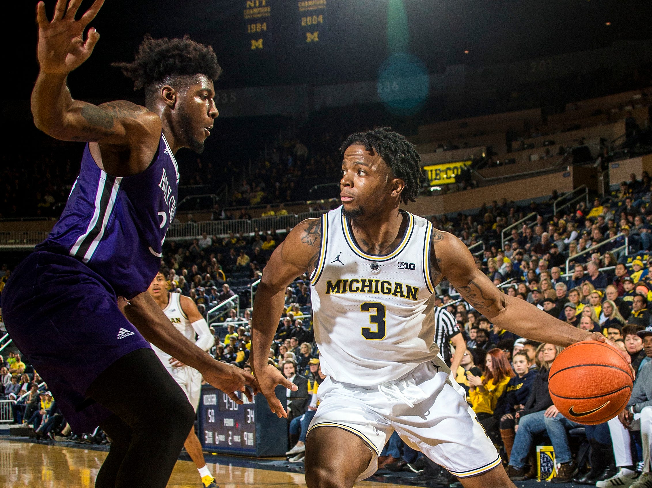 Holy Cross forward Jehyve Floyd, left, defends against Michigan guard Zavier Simpson (3), in the second half of an NCAA college basketball game at Crisler Center in Ann Arbor, Mich., Saturday, Nov. 10, 2018. (AP Photo/Tony Ding)