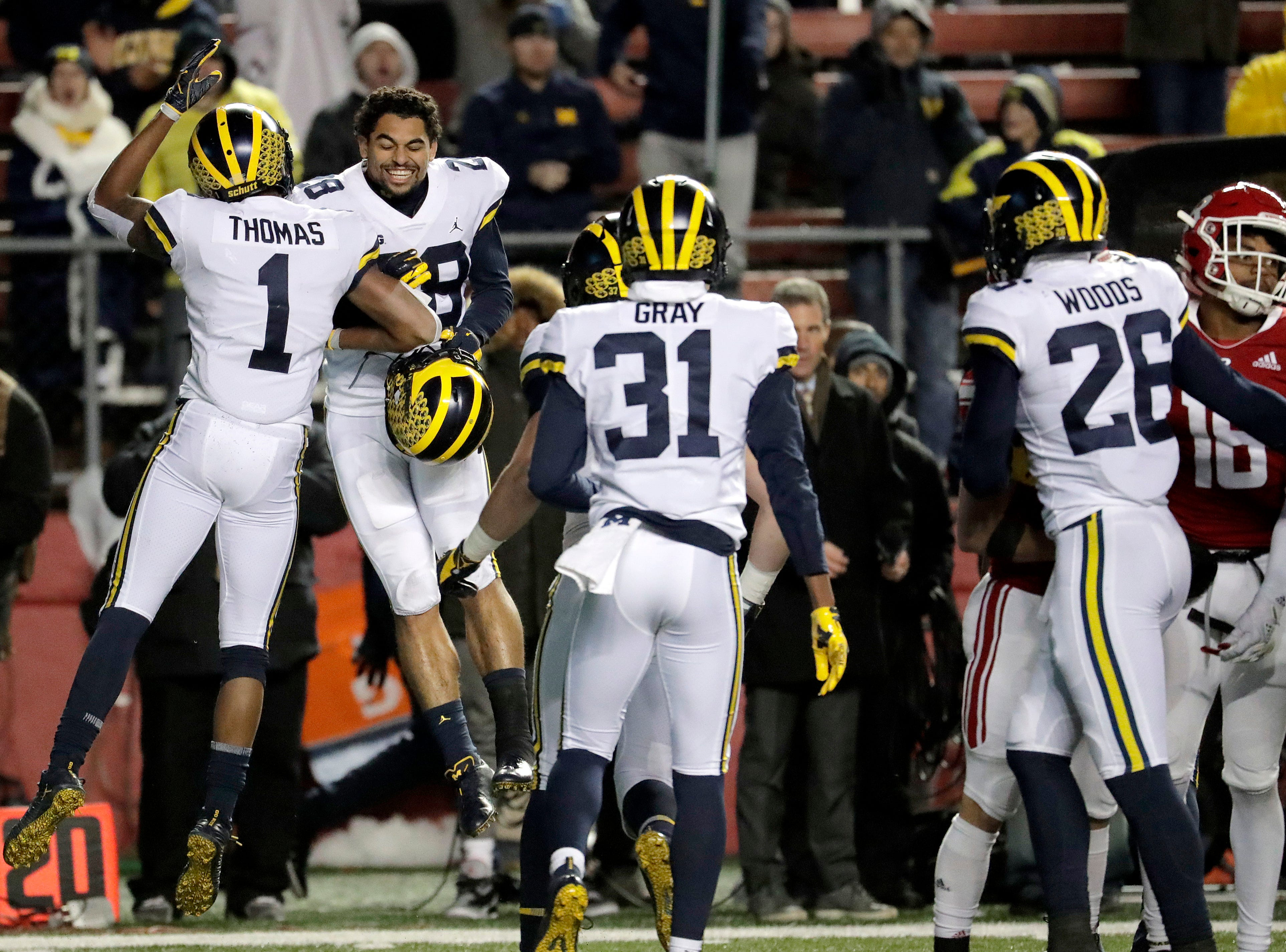 Michigan defensive back Ambry Thomas (1) celebrates his interception with defensive back Brandon Watson.