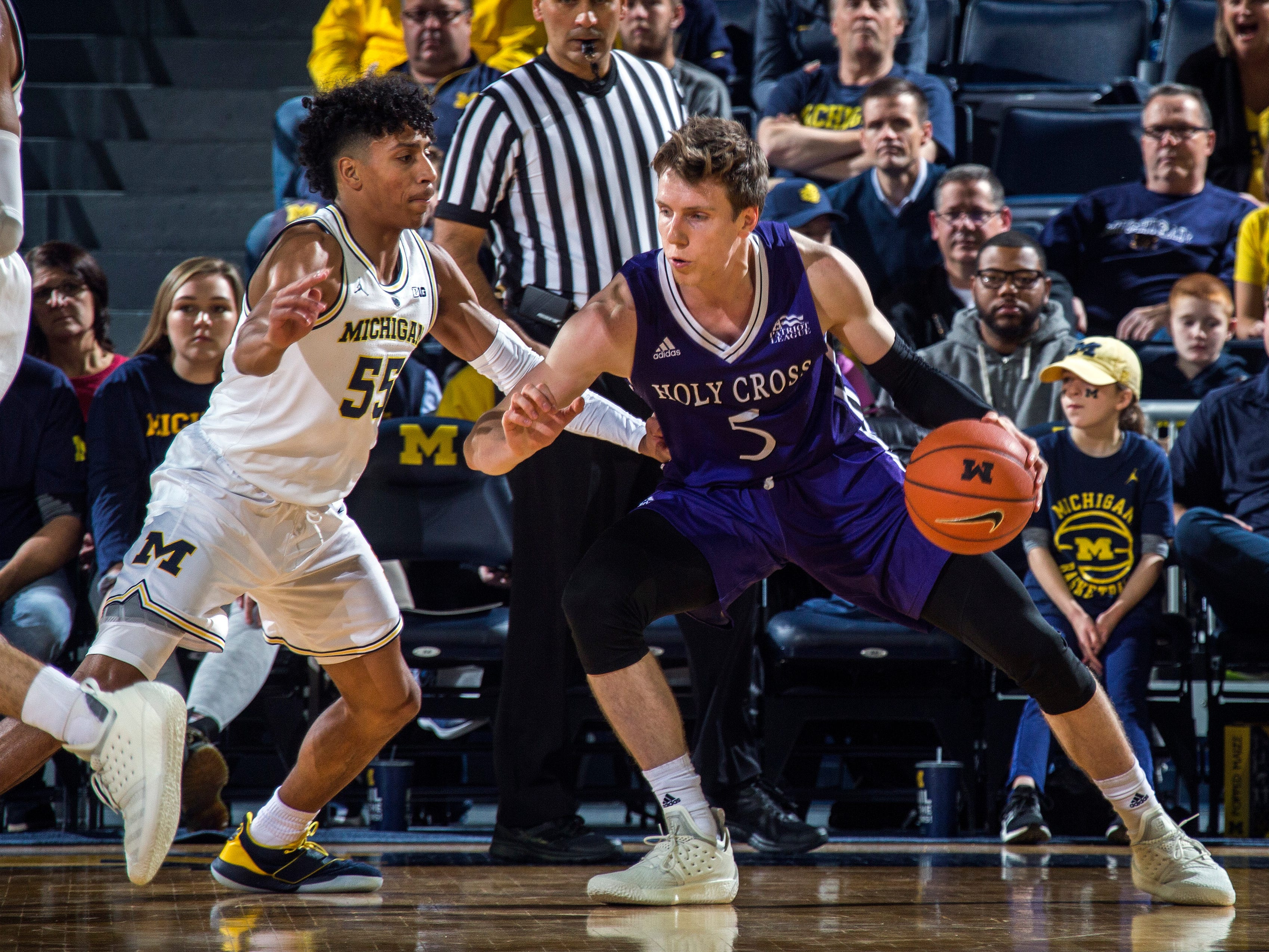 Michigan guard Eli Brooks (55) defends Holy Cross forward Connor Niego (5) in the second half of an NCAA college basketball game at Crisler Center in Ann Arbor, Mich., Saturday, Nov. 10, 2018. Michigan won 56-37. (AP Photo/Tony Ding)