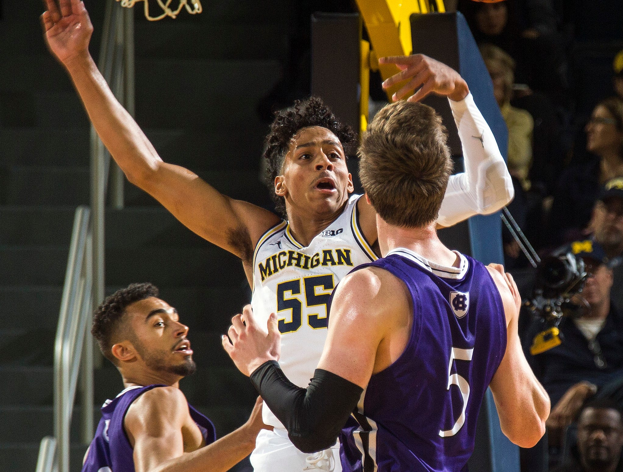 Michigan guard Eli Brooks (55) tries to intercept a pass from Holy Cross forward Connor Niego (5) to guard Kyle Copeland, left, during the first half of an NCAA college basketball game in Ann Arbor, Mich., Saturday, Nov. 10, 2018. (AP Photo/Tony Ding)