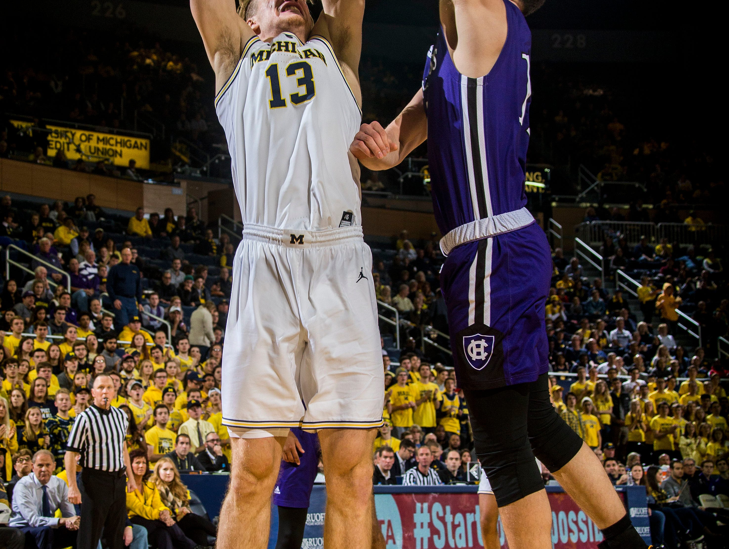 Michigan forward Ignas Brazdeikis (13) goes to the basket while defended by Holy Cross forward Matt Faw, right, in the second half of an NCAA college basketball game at Crisler Center in Ann Arbor, Mich., Saturday, Nov. 10, 2018. (AP Photo/Tony Ding)