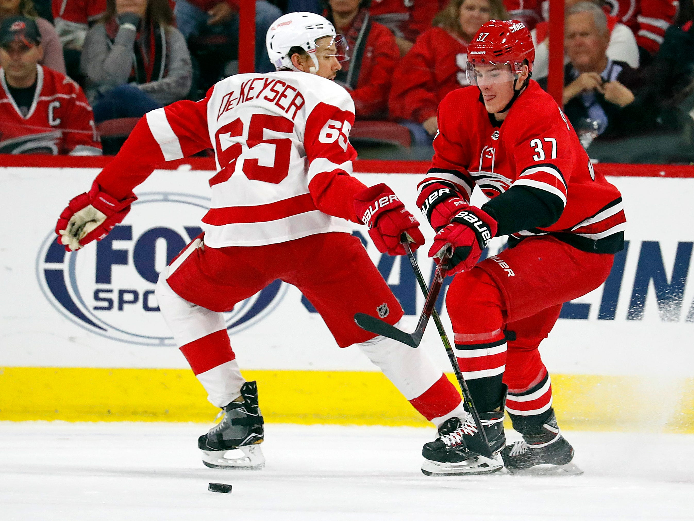 Carolina Hurricanes' Andrei Svechnikov (37) works against Detroit Red Wings' Danny DeKeyser (65) during the first period.