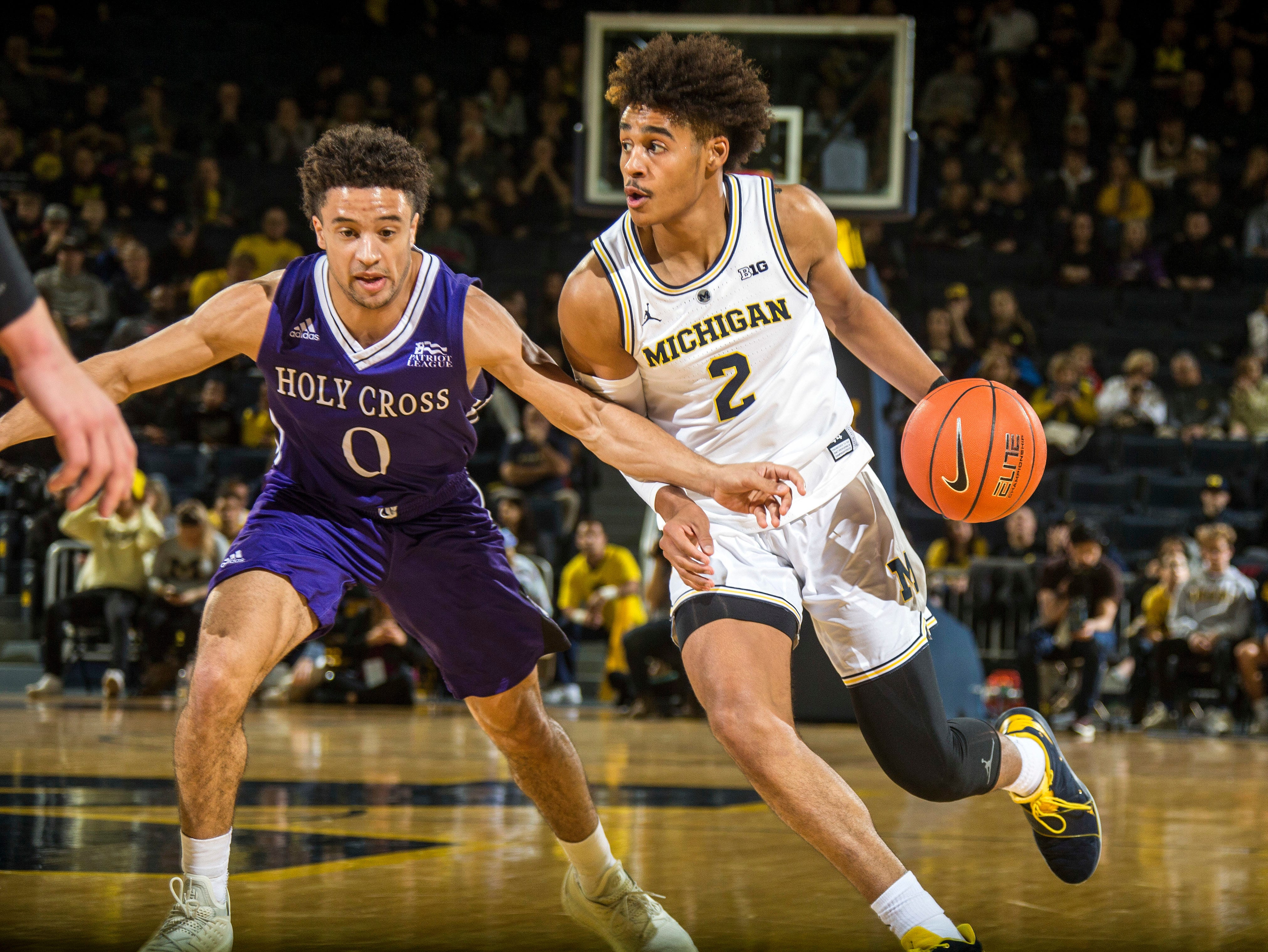 Holy Cross guard Caleb Green (0) defends Michigan guard Jordan Poole (2) in the first half of an NCAA college basketball game at Crisler Center in Ann Arbor, Mich., Saturday, Nov. 10, 2018. Michigan won 56-37. (AP Photo/Tony Ding)