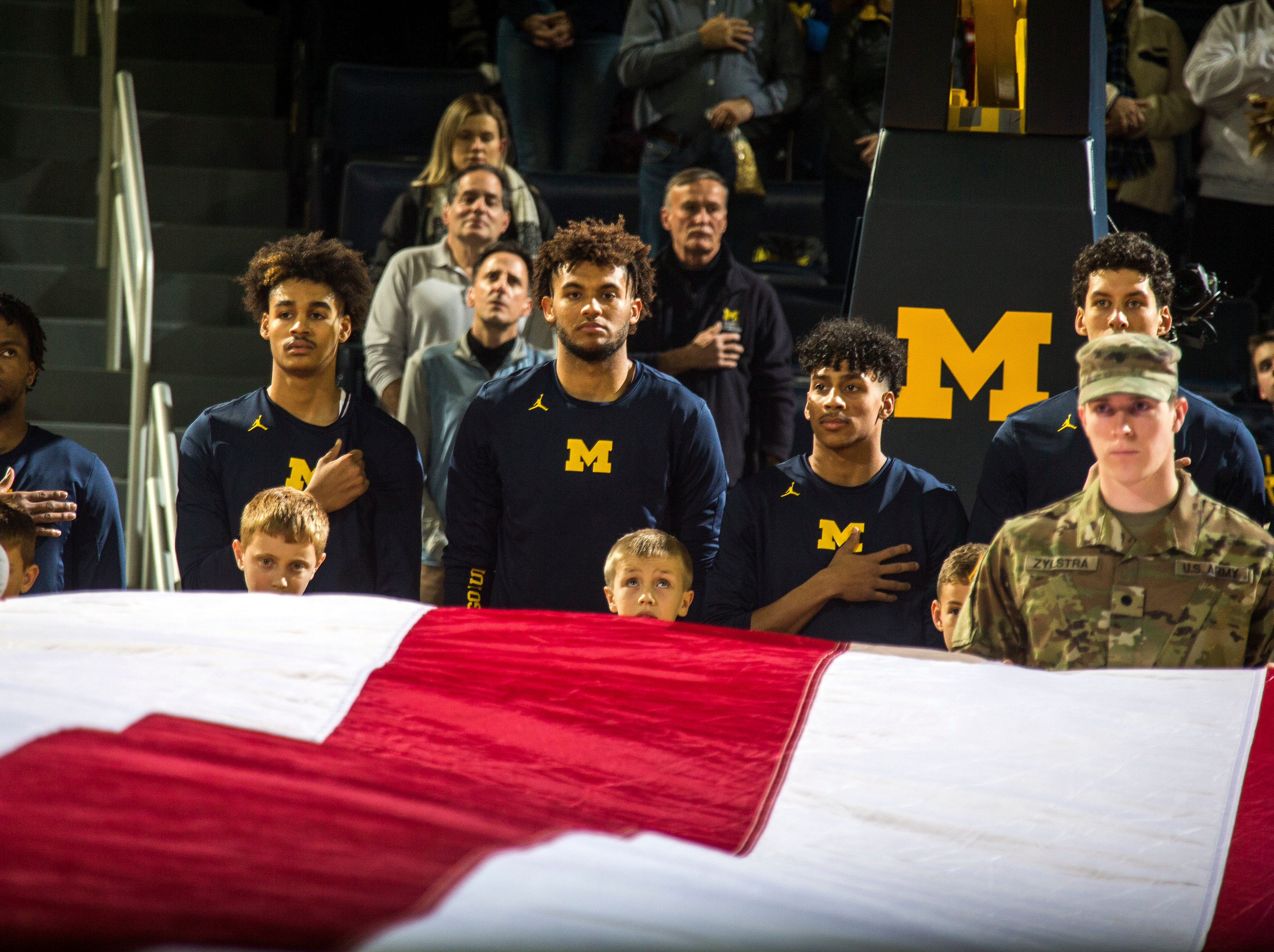 Michigan players line up on the court opposite Holy Cross players with a large American flag held across the court for the playing for the national anthem, before an NCAA college basketball game at Crisler Center in Ann Arbor, Mich., Saturday, Nov. 10, 2018. (AP Photo/Tony Ding)