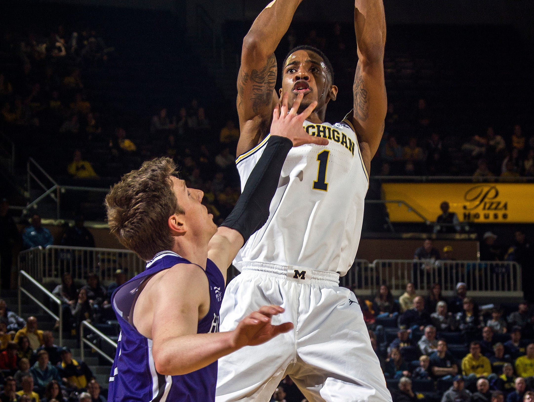 Holy Cross forward Connor Niego (5) defends against a shot-attempt by Michigan guard Charles Matthews (1) in the second half of an NCAA college basketball game at Crisler Center in Ann Arbor, Mich., Saturday, Nov. 10, 2018. (AP Photo/Tony Ding)