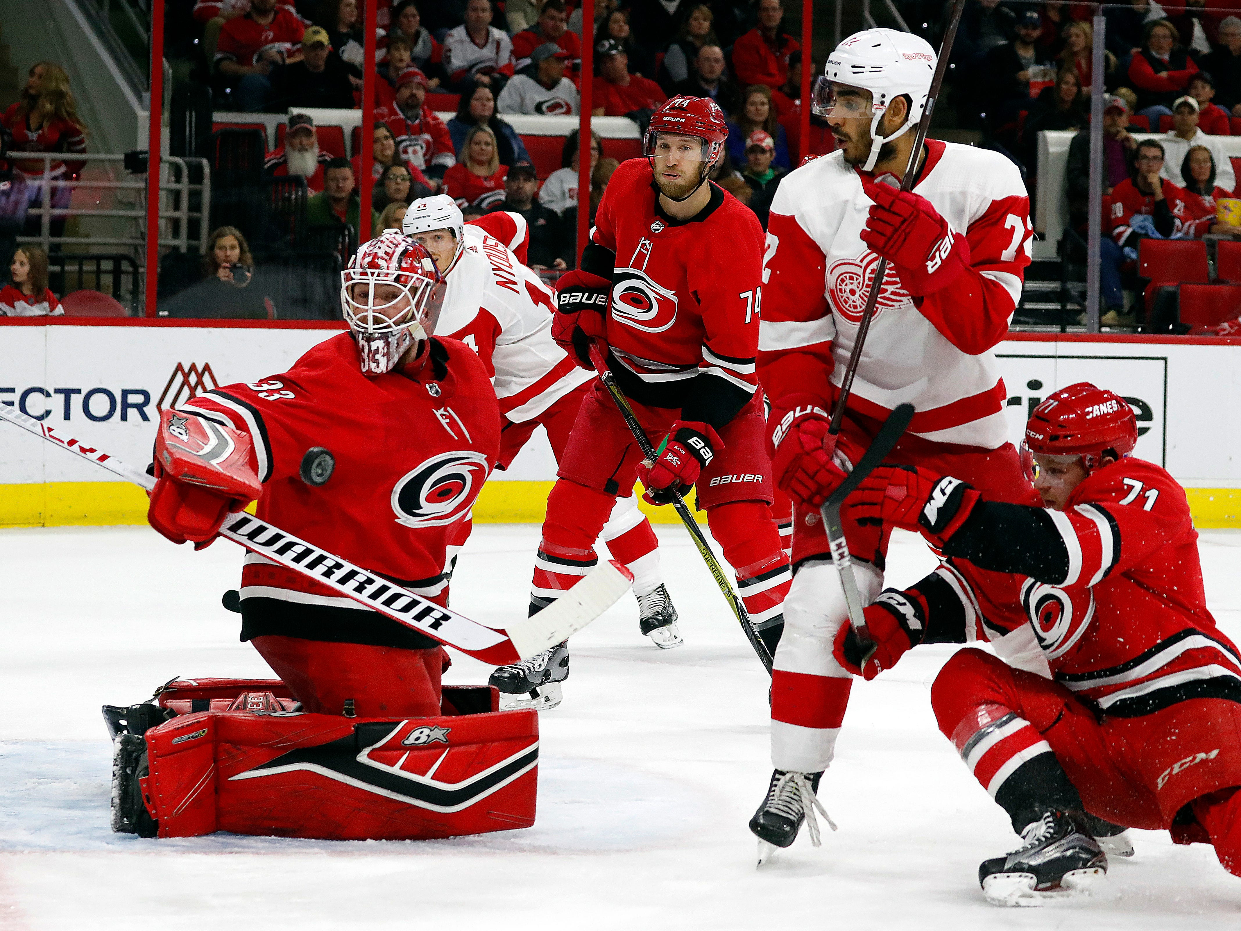 Carolina Hurricanes goaltender Scott Darling (33) watches the puck come off the post with Hurricanes' Lucas Wallmark (71) and Detroit Red Wings' Andreas Athanasiou (72) battling nearby during the second period.