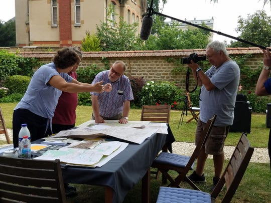 Nancy Hasting, left, Richard Tucker and Chris Sims discuss the route that Chester Schulz took in northern France as filmmaker Brick Briscoe records the scene.