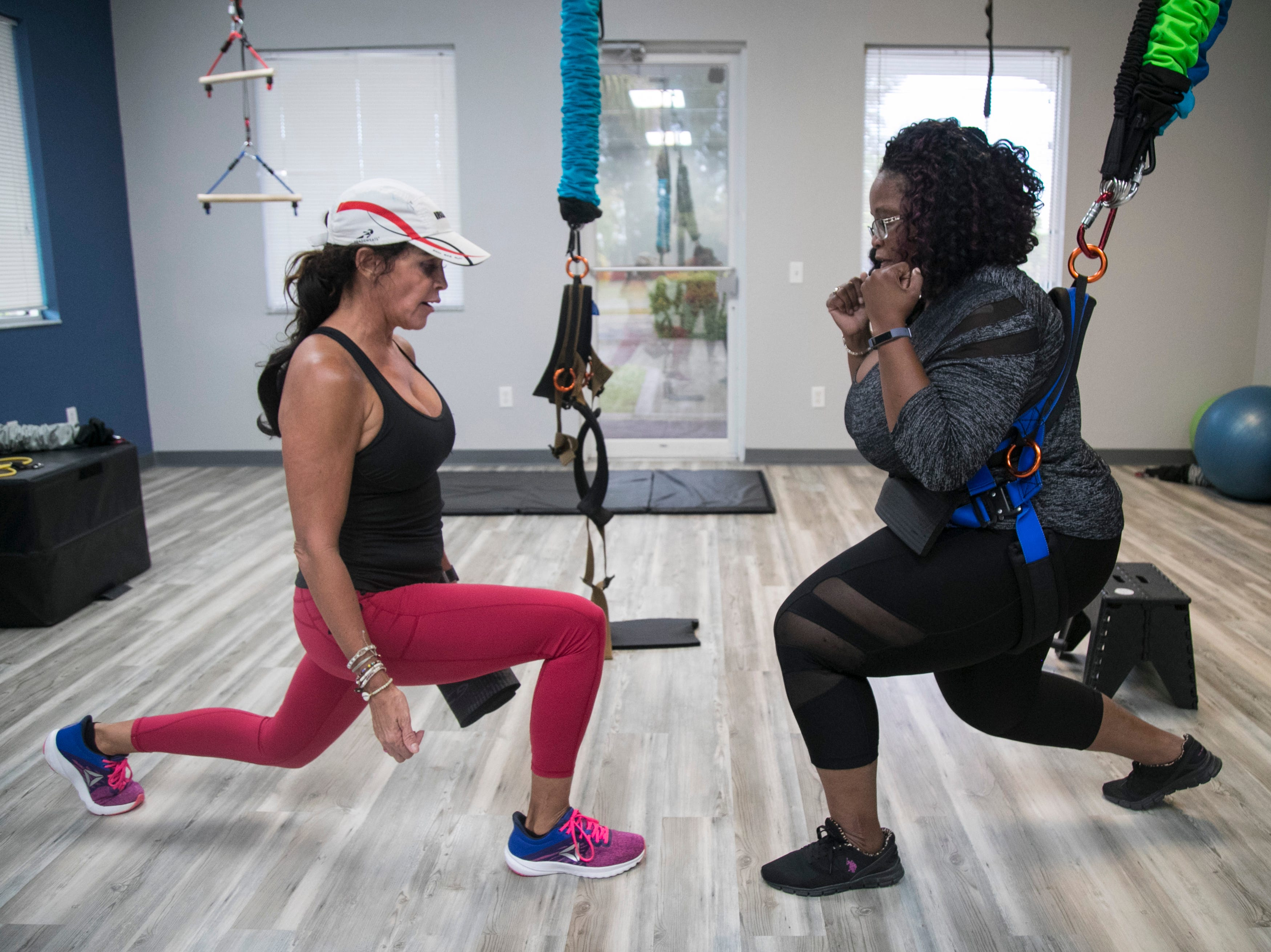 Sabrina Kempa, left, coaches Vanessa Vance on the proper technique for lunges on the Astro-Durance bungee at P2 Personal Training in Cape Coral on Wednesday.