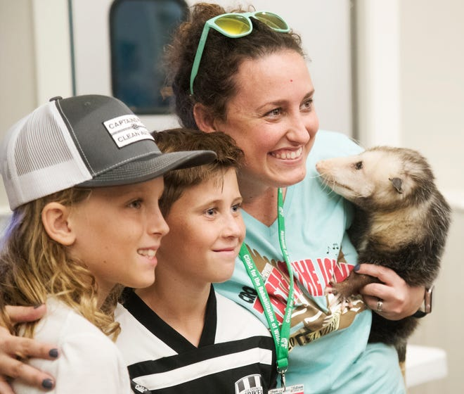 Matthew Huff, 10, left, and Vance Byrd, 10, meet Rachel Rainbolt, of The Clinic for the Rehabilitation of Wildlife (CROW), and Bashful, an opossum on Sunday at the Taste of the Islands event at Sanibel Community Park. The annual event features food from 13 island eateries and benefits CROW.