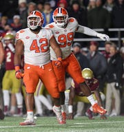 Clemson defensive lineman Christian Wilkins (42) celebrates with defensive lineman Clelin Ferrell (99) after bringing down Boston College quarterback Anthony Brown (13) during the 1st quarter at Boston College's Alumni Stadium in Chestnut Hill, MA. Saturday, November 10, 2018.