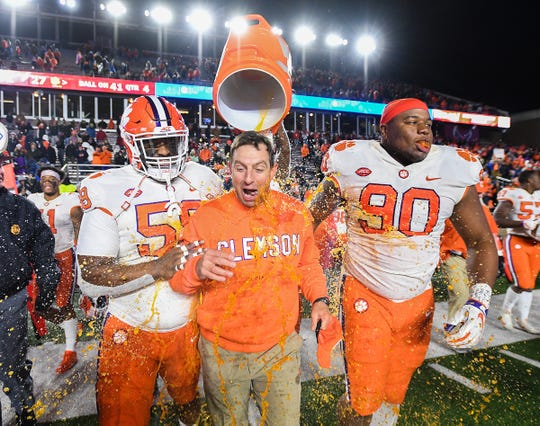 Clemson defensive lineman Christian Wilkins, back douses head coach Dabo Swinney with Gatorade after the Tiger defeated Boston College 27-7 to win the Atlantic Division at Boston College's Alumni Stadium in Chestnut Hill, MA. Saturday, November 10, 2018. Also pictured are defensive linemen Jordan Williams, left, and Dexter Lawrence.
