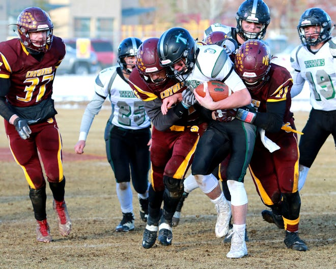 Flint Creek ball carrier Kade Cutler is tackled by Shelby defenders Ryan Van Tine (21) and Tanner Parsons (21), with Shelby's Dillon Luly (37) looking on during Flint Creek's 28-20 win over the Coyote in Saturday's Class C semifinals.