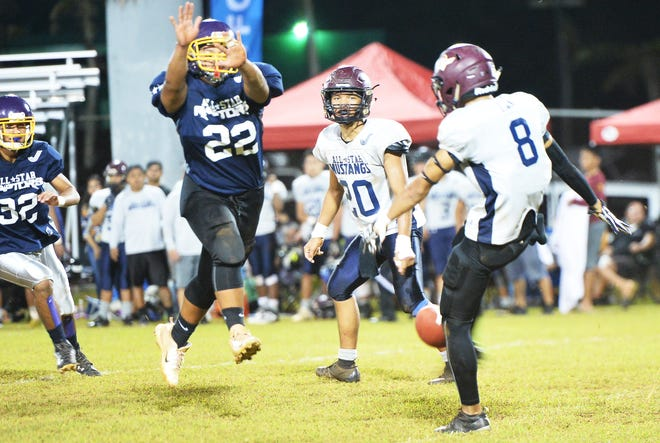 The Raptors' Josh Dela Cruz, 22, sets up perfectly to block Mustangs punter Noah Diaz in the second quarter of the Triple J High School Football All-Star game Nov. 10 at Angels Field in Dededo.  Dela Cruz not only blocked the punt, he picked up the wayward ball and ran it in for a 14-yard touchdown for the game's first score.