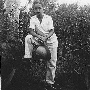 """13-year-old Vincente """"Ben"""" T. Blaz poses for a photo at the family farm after the liberation of Guam from Japanese occupation during World War II. Blaz, who later became a brigadier general in the Marine Corps, is holding a Marine pith helmet given to him by Marines whom he spent time with after the war. It was his treasured possession, his source of pride, and symbolized his desire to become a Marine, according to family members. Throughout the years after he retired from the Marine Corps, Blaz would wear one of these helmets when he worked outdoors."""