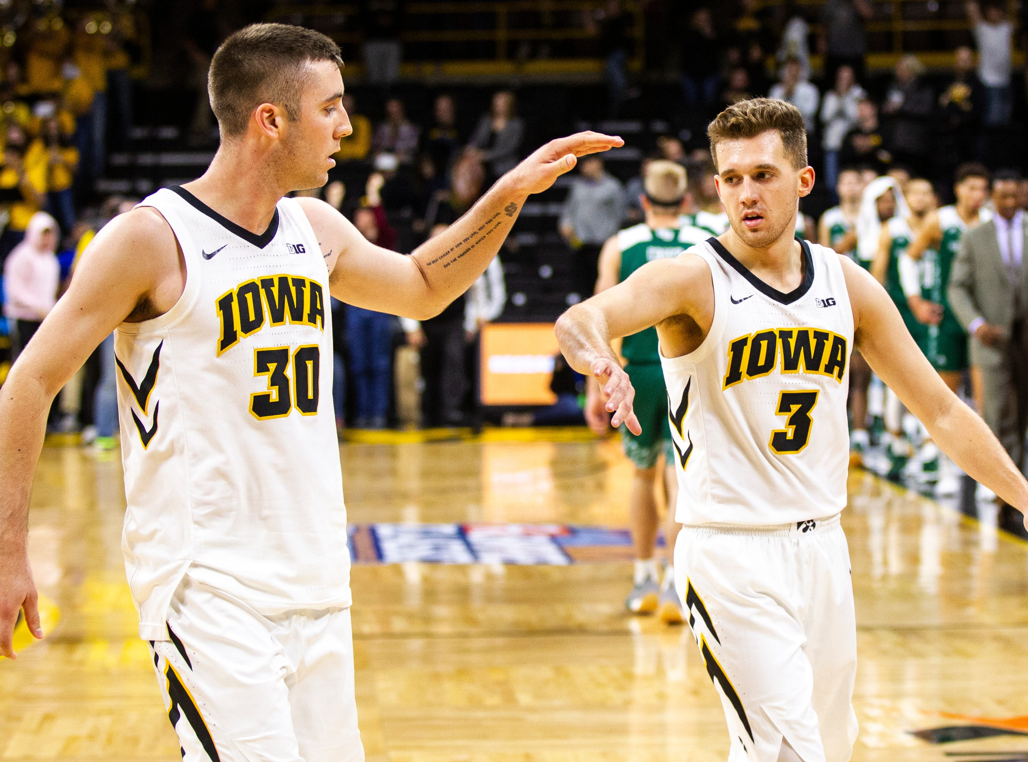 Iowa guard Connor McCaffery (30) high-fives Iowa guard Jordan Bohannon (3) after an NCAA men's basketball game in the 2K Empire Classic on Sunday, Nov. 11, 2018, at Carver-Hawkeye Arena in Iowa City.