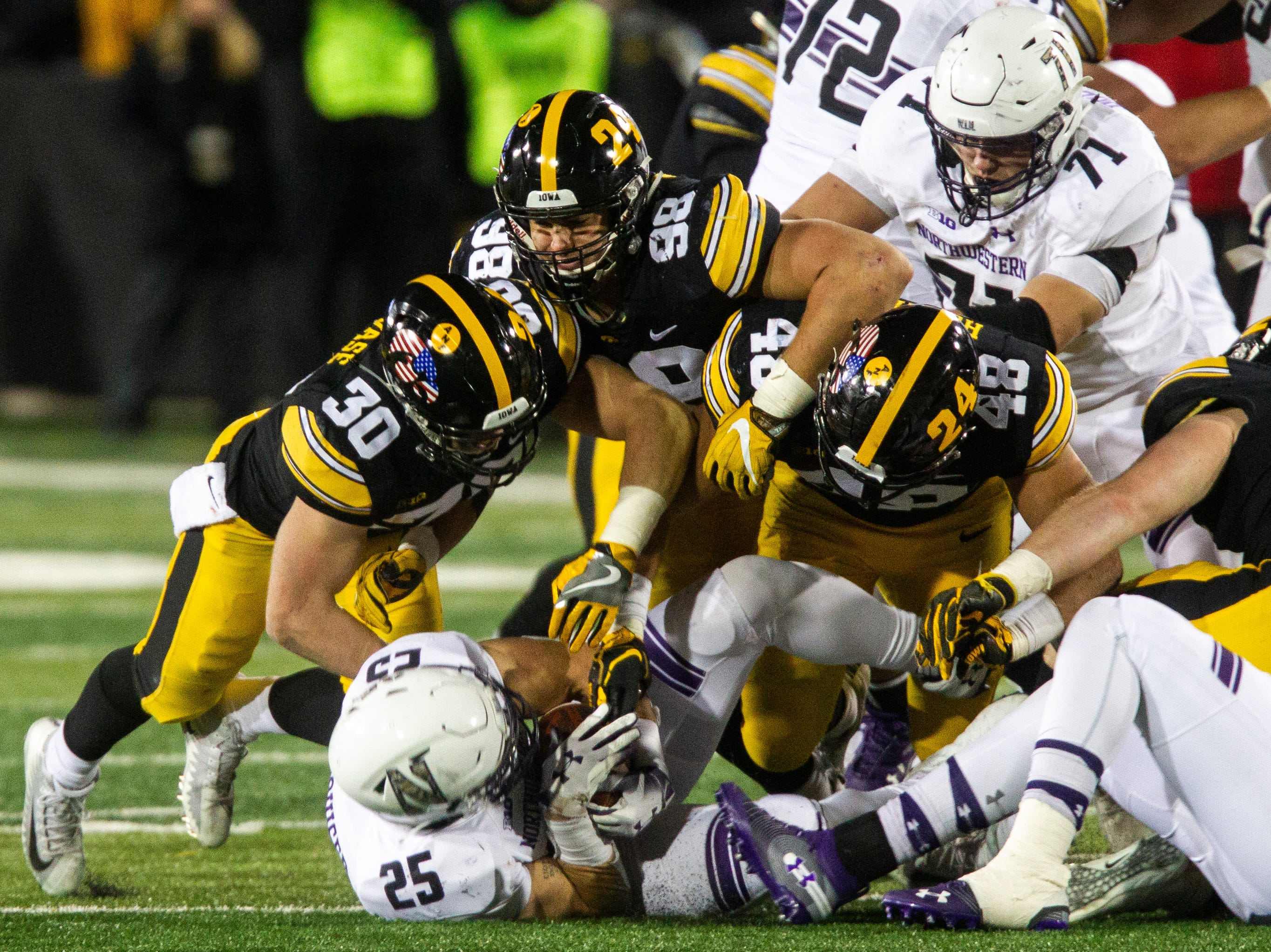 Iowa defensive back Jake Gervase (30) defensive end Anthony Nelson (98) linebacker Jack Hockaday (48) tackle Northwestern's Isaiah Bowser (25) during a Big Ten Conference football game on Saturday, Nov. 10, 2018, at Kinnick Stadium in Iowa City.