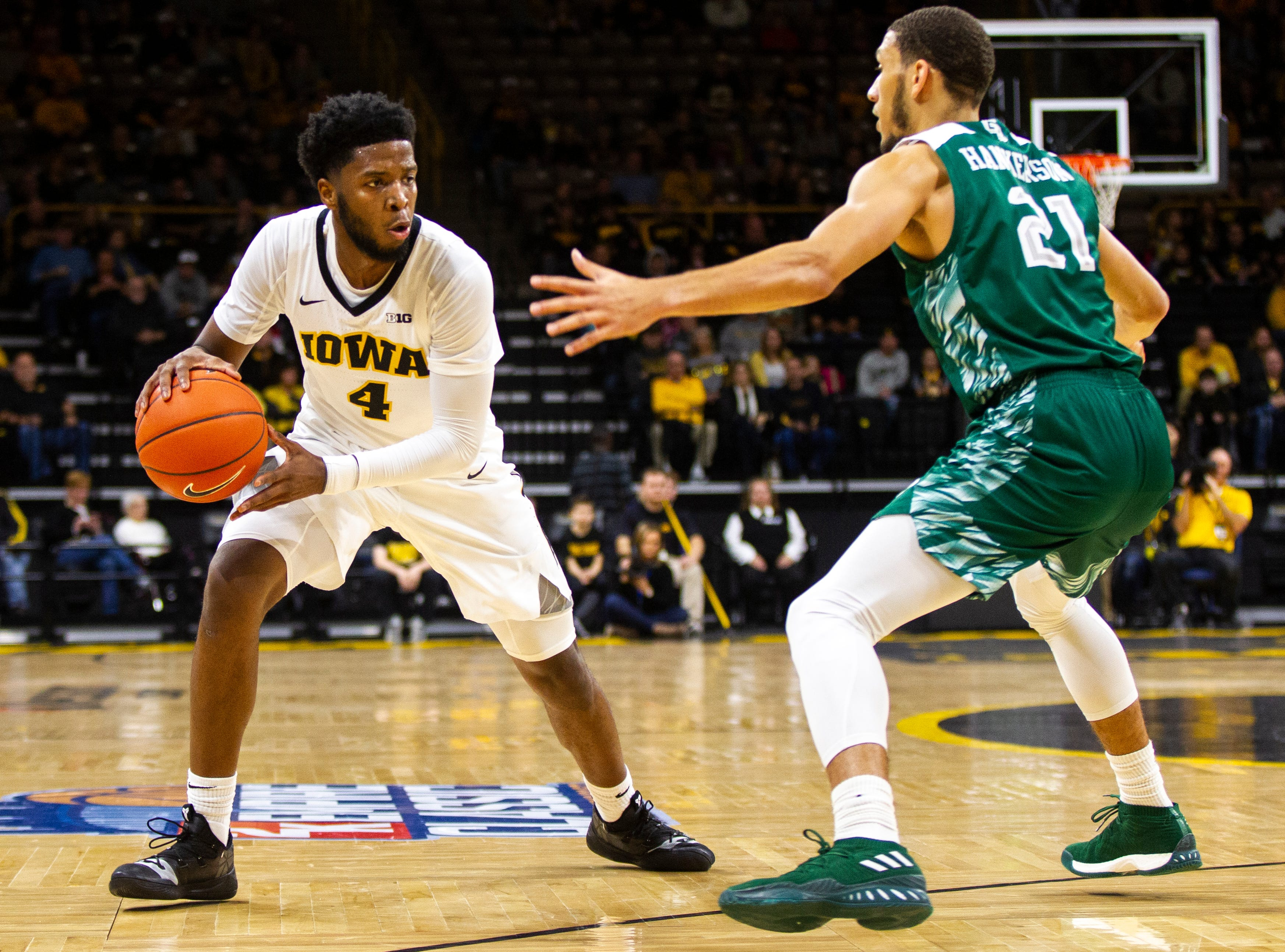 Iowa guard Isaiah Moss (4) dribbles past Green Bay guard Kam Hankerson (21) during an NCAA men's basketball game in the 2K Empire Classic on Sunday, Nov. 11, 2018, at Carver-Hawkeye Arena in Iowa City.