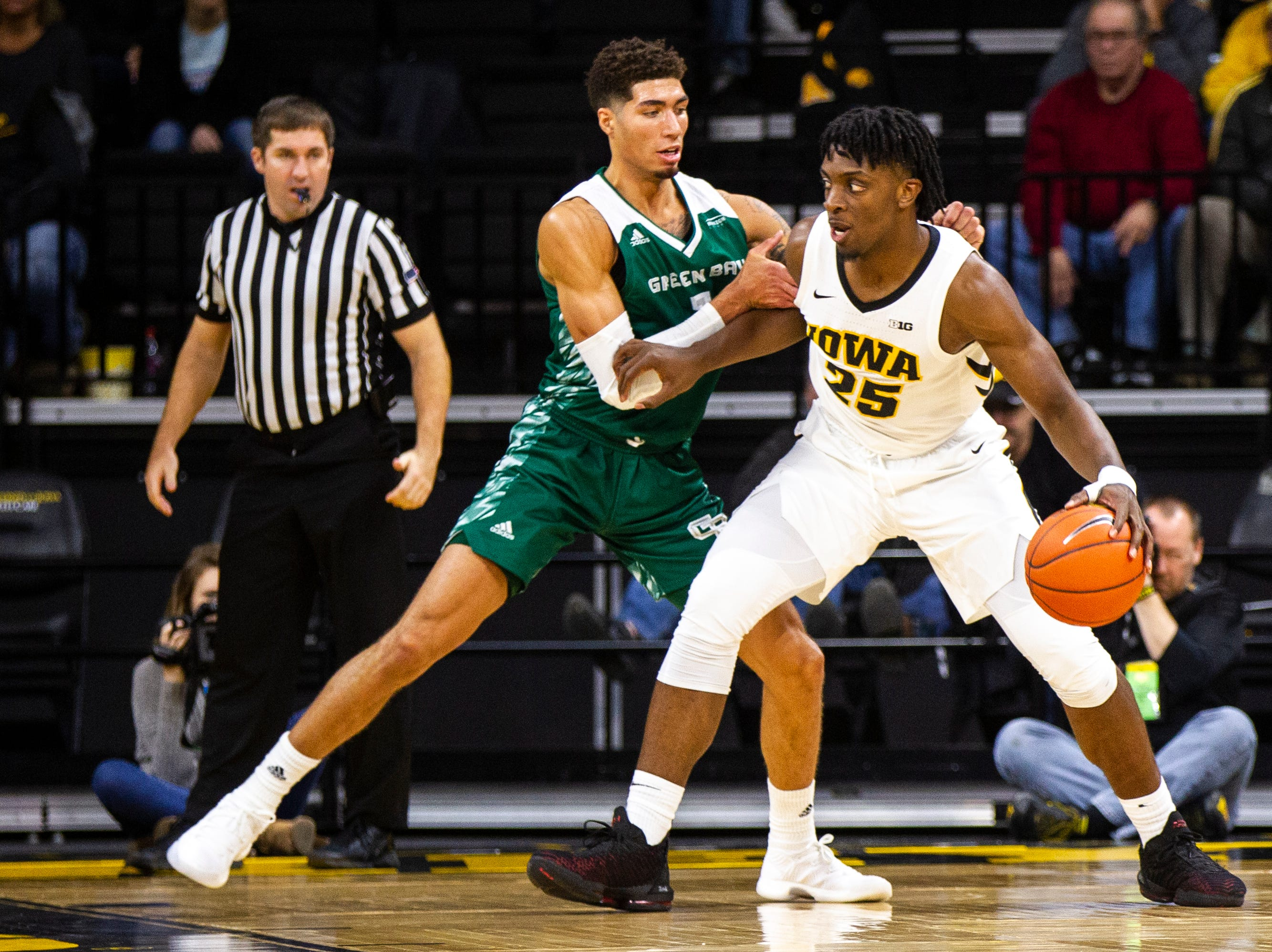 Iowa forward Tyler Cook (25) drives while being guarded by Green Bay guard Sandy Cohen III (1) during an NCAA men's basketball game in the 2K Empire Classic on Sunday, Nov. 11, 2018, at Carver-Hawkeye Arena in Iowa City.