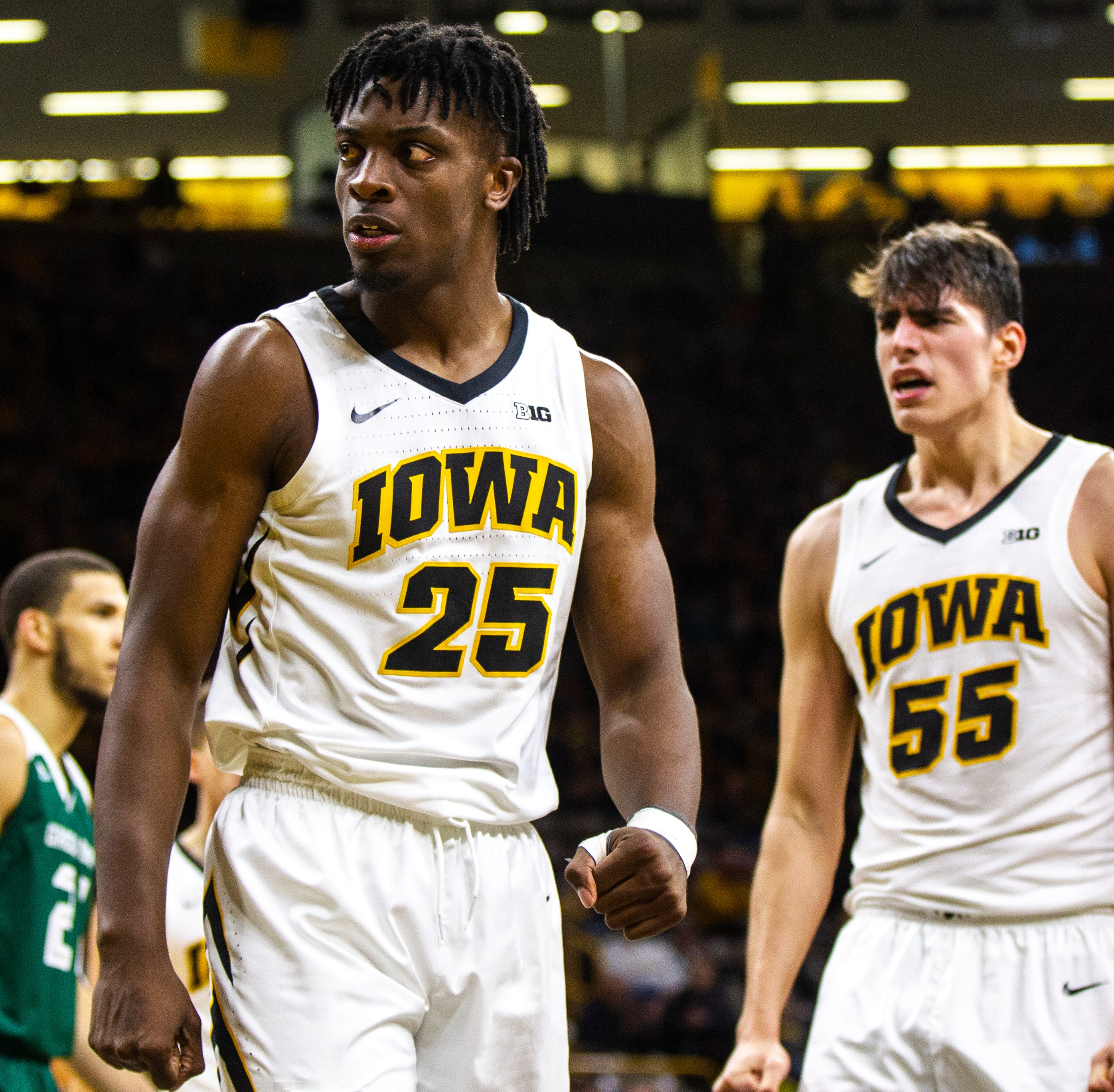 Iowa forward Tyler Cook (25) stares down Green Bay guard Cody Schwartz (33) after dunking over him during an NCAA men's basketball game in the 2K Empire Classic on Sunday, Nov. 11, 2018, at Carver-Hawkeye Arena in Iowa City.