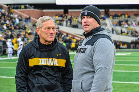 Iowa coach Kirk Ferentz (left) and Northwestern coach Pat Fitzgerald converse before Saturday's game.