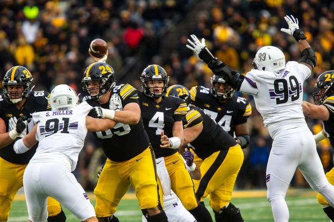 Iowa quarterback Nate Stanley (4) tries to get a pass out while Northwestern defensive lineman Jordan Thompson (99) gets his hands up during a Big Ten Conference football game on Saturday, Nov. 10, 2018, at Kinnick Stadium in Iowa City.
