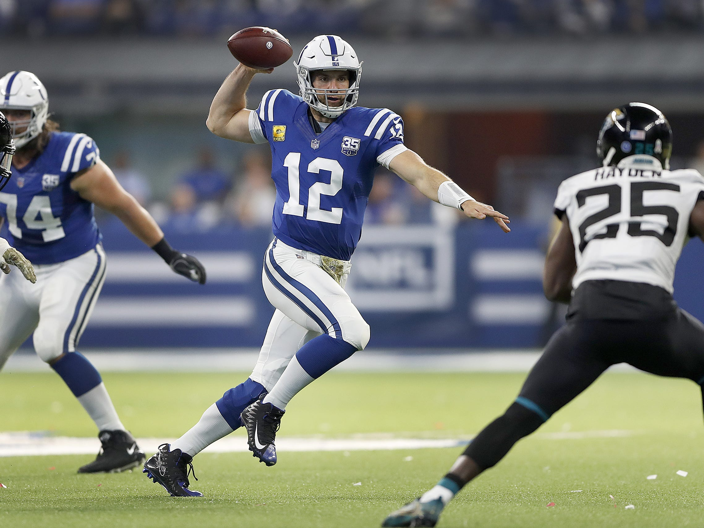 Indianapolis Colts quarterback Andrew Luck (12) scrambles and passes the football in the first half of their game at Lucas Oil Stadium on Sunday, Nov. 11, 2018.