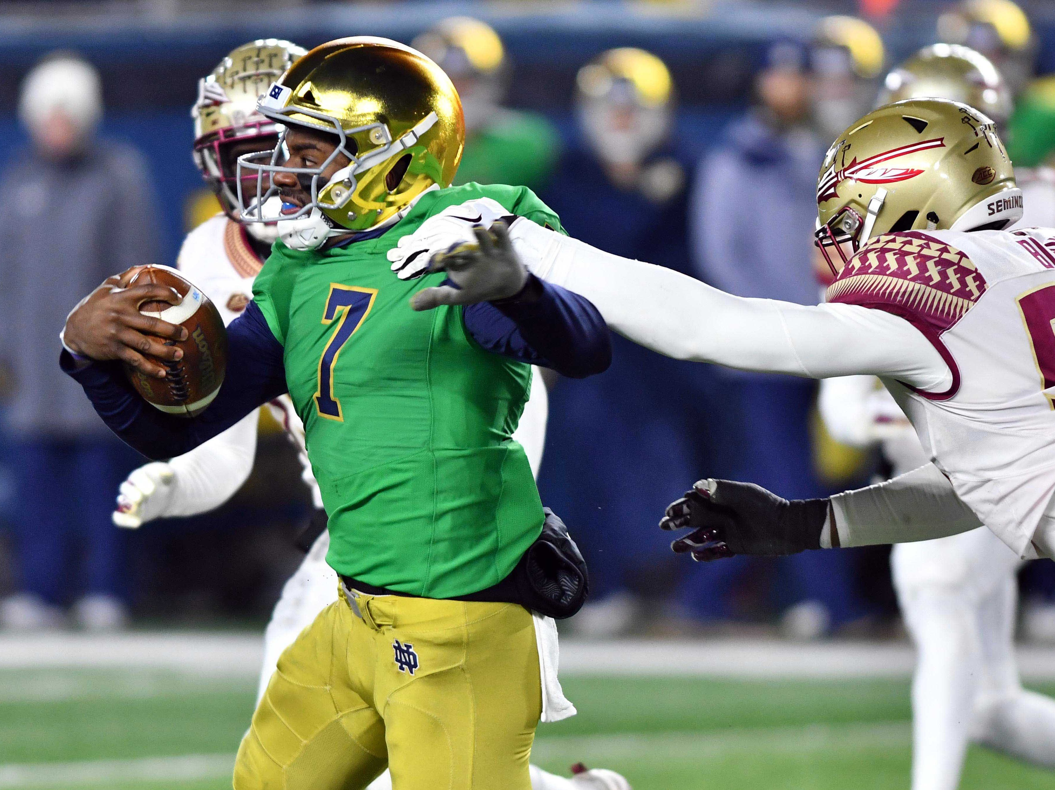 Nov 10, 2018; South Bend, IN, USA; Notre Dame Fighting Irish quarterback Brandon Wimbush (7) runs the ball as Florida State Seminoles defensive end Brian Burns (99) attempts to tackle in the second quarter at Notre Dame Stadium. Mandatory Credit: Matt Cashore-USA TODAY Sports