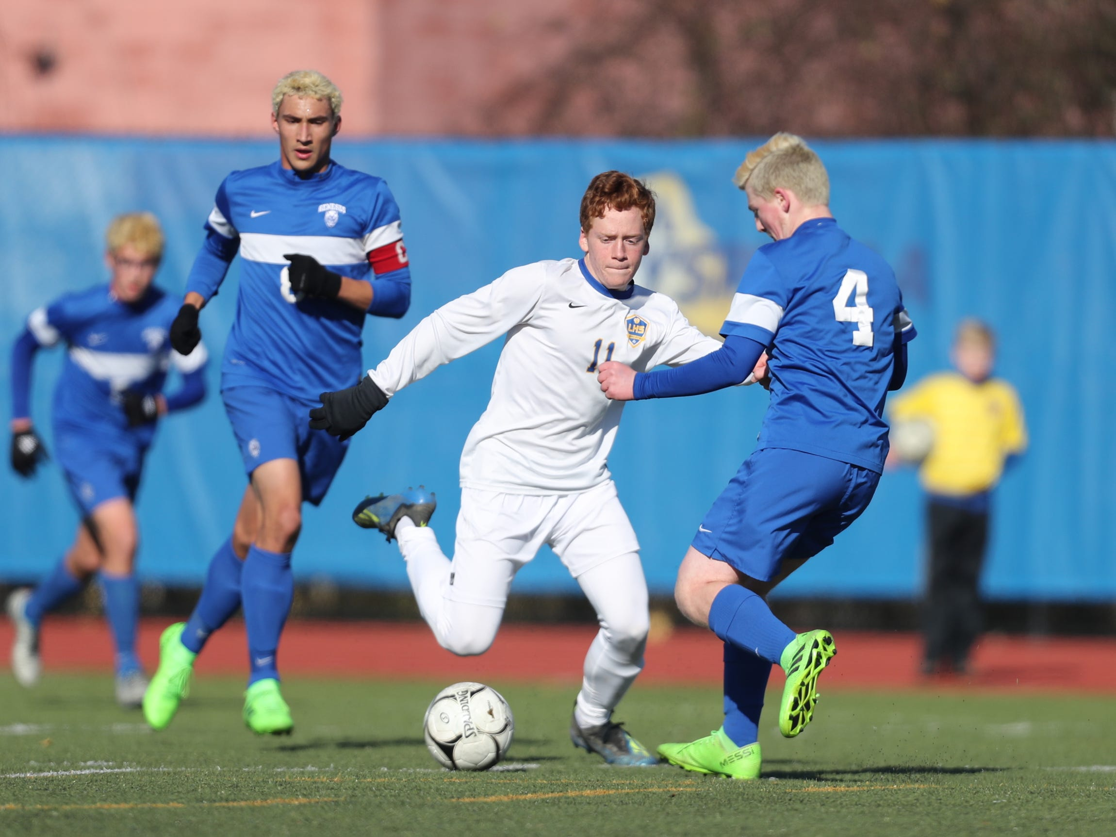 Lansing's Kyle Romeo (11) and Jonathan Edmunds (4) battle for possession during the Class C boys state soccer final at Middletown High School in Middletown on Sunday, November 11, 2018.  Lansing won 3-0.