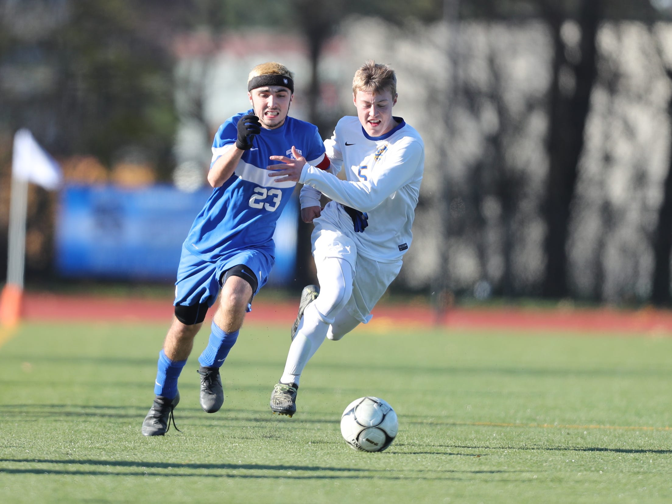 Lansing's Ethan Zemanick (5) and Geneseo's Camden Malone (23) battle for possession during the Class C boys state soccer final at Middletown High School in Middletown on Sunday, November 11, 2018.  Lansing won 3-0.