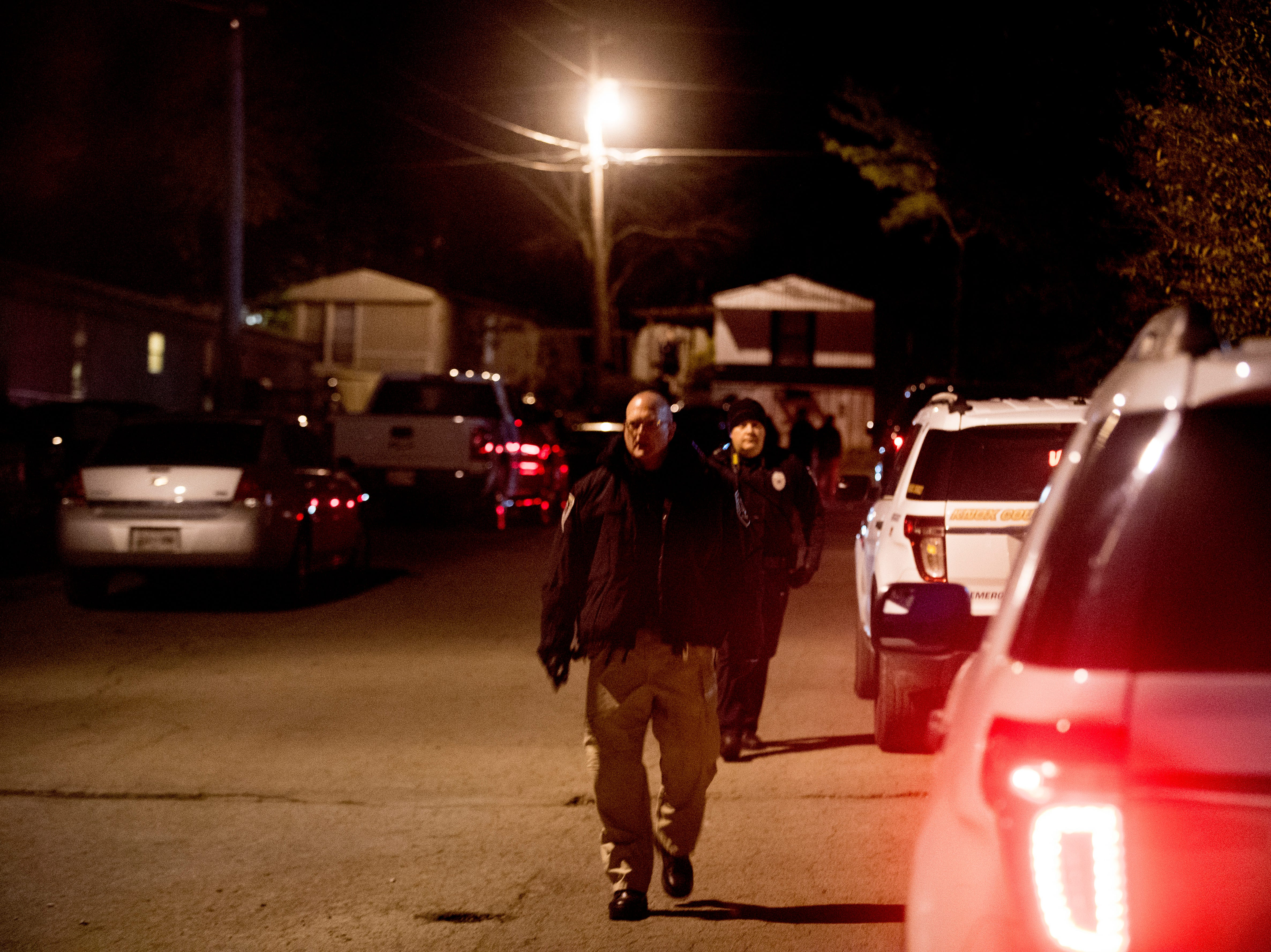 An investigator walks at the scene of a shooting on Forest Edge Way in Knoxville, Tennessee on Saturday, November 10, 2018. One victim was confirmed dead at the scene and a second injured.