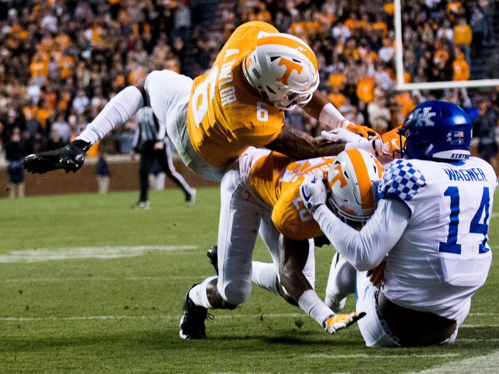 Kentucky wide receiver Ahmad Wagner (14) falls to the ground as Tennessee defensive back Baylen Buchanan (28) and Tennessee defensive back/wide receiver Alontae Taylor (6) defend during a game between Tennessee and Kentucky at Neyland Stadium in Knoxville, Tennessee on Saturday, November 10, 2018.