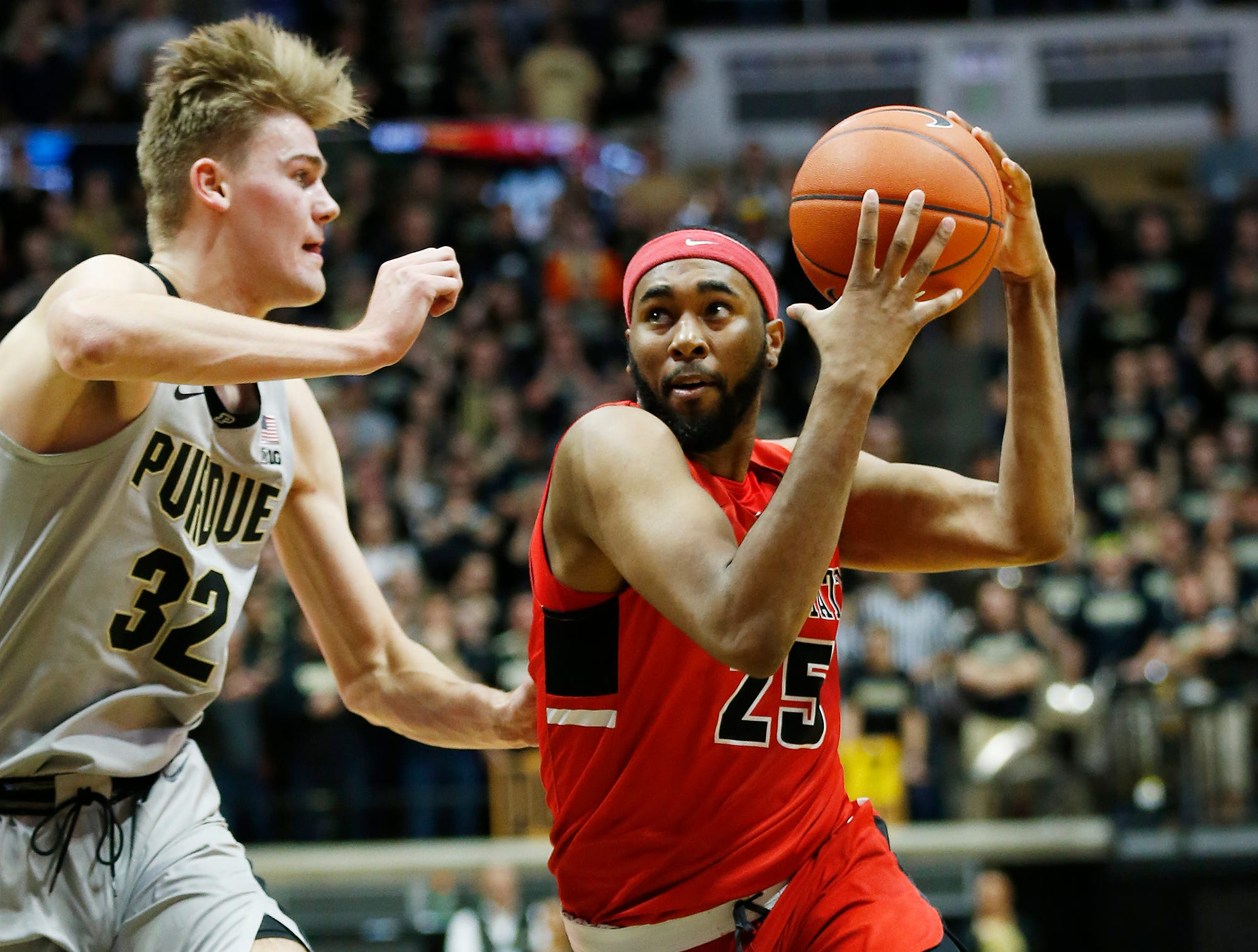 Tahjai Teague of Ball State with a drive to the basket against Matt Haarms of Purdue Saturday, November 10, 2018, at Mackey Arena.