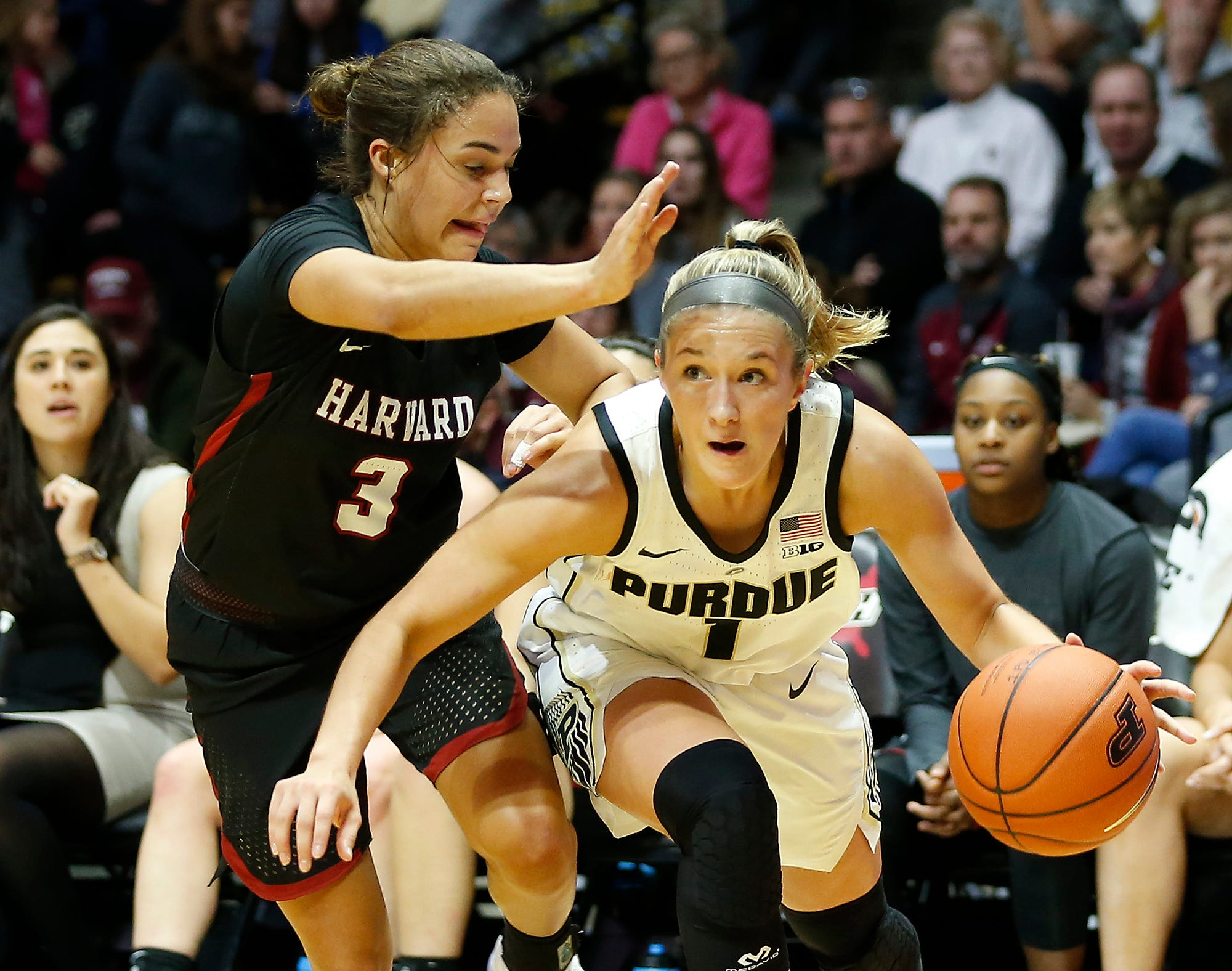 Purdue guard Karissa McLauglin slips beneath Katie Benzan of Harvard on a drive along the baseline.